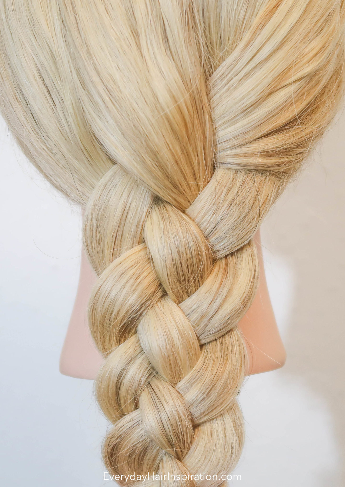 Picture of a hairdresser doll, with a 4 strand flat braid, braided in the hair.