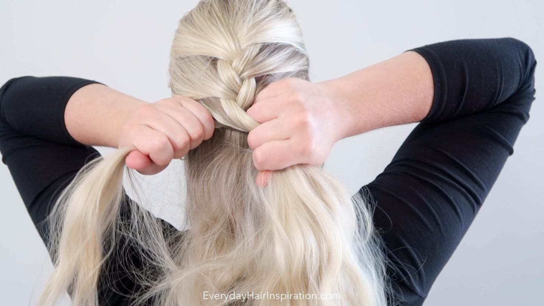 Woman French braiding her own hair in a single braid