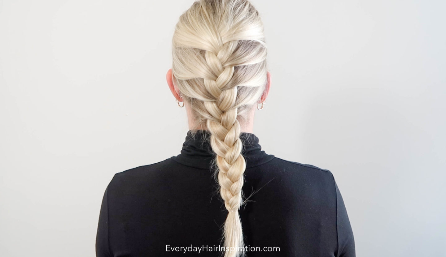 Woman sitting with the back to the camera, the hair is braided in a french braid