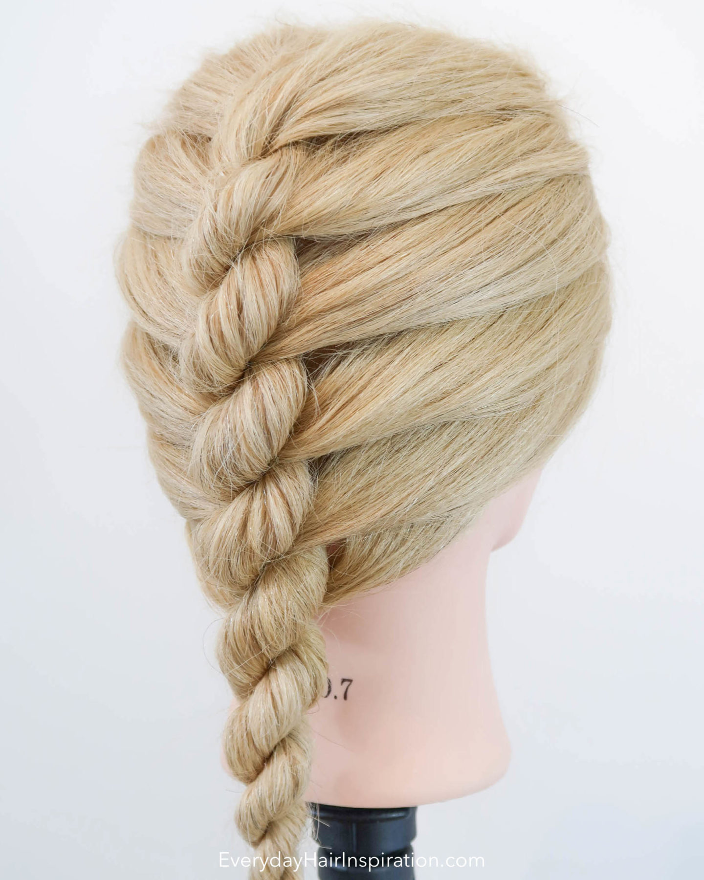 Blonde hairdresser doll with a single french rope braid in the hair - looking at the braid from a side angle.