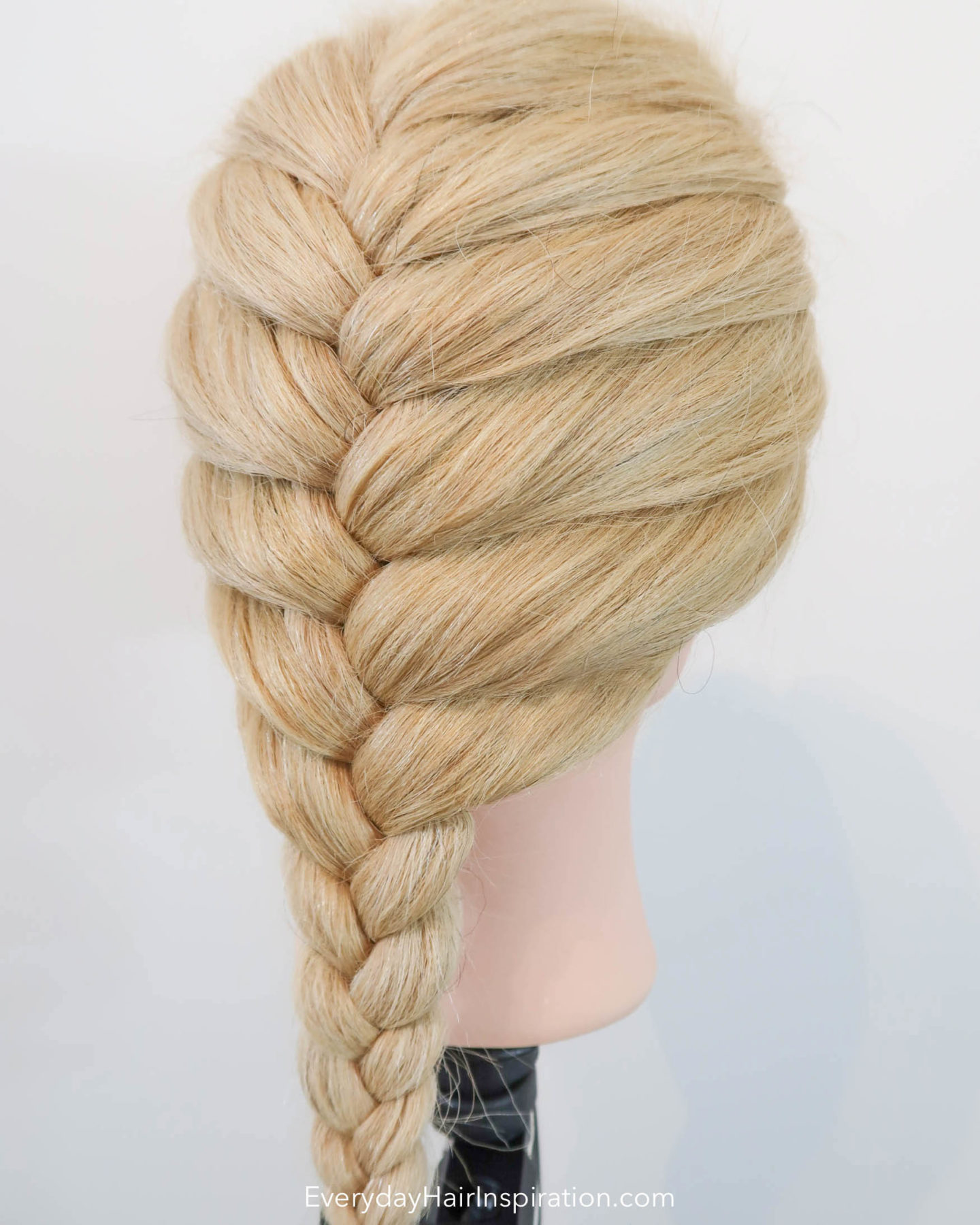 Blonde hairdresser doll. Slight side profile of a single French braid