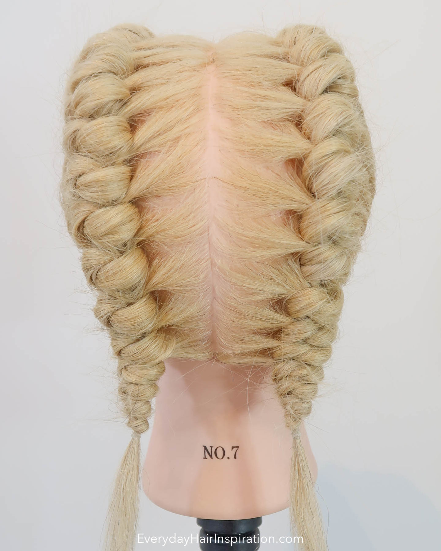 Blonde hairdresser head, seen from the back with double knot braids