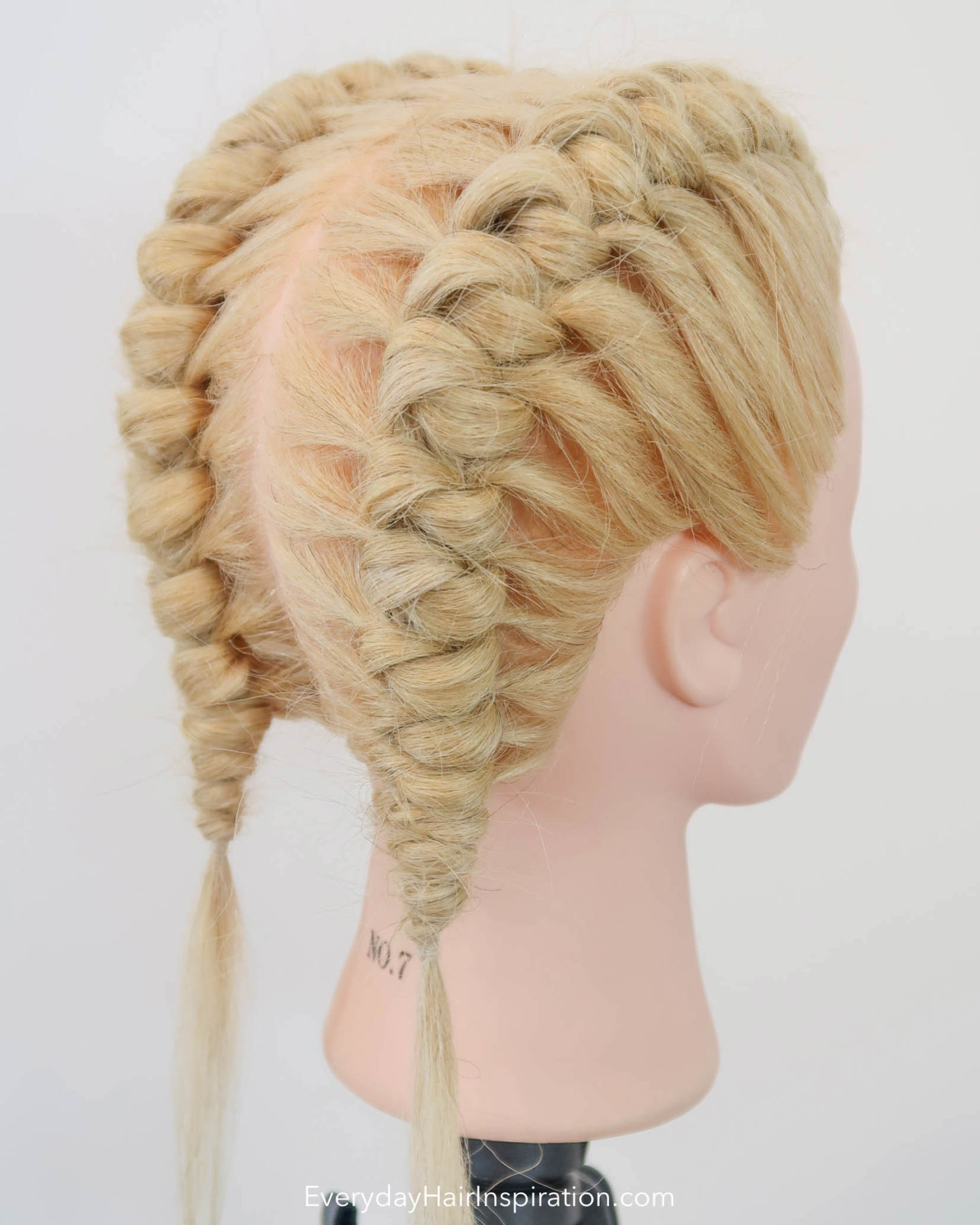 Blonde hairdresser head, seen from the side with double knot braids