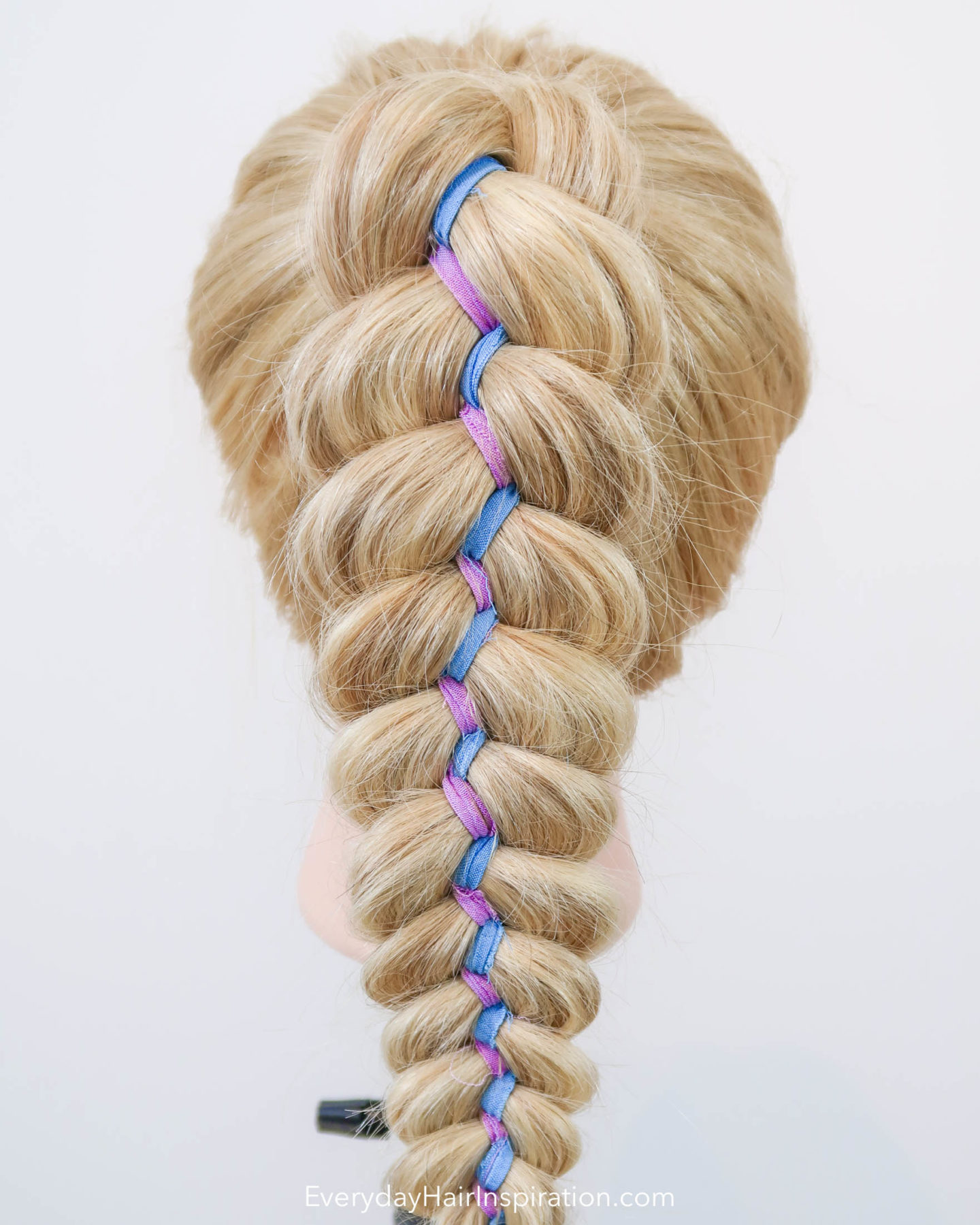 Close up of a blonde hairdresser doll with a high ponytail, in which there is a 5 strand ribbon braid, with purple and blue colored ribbon.