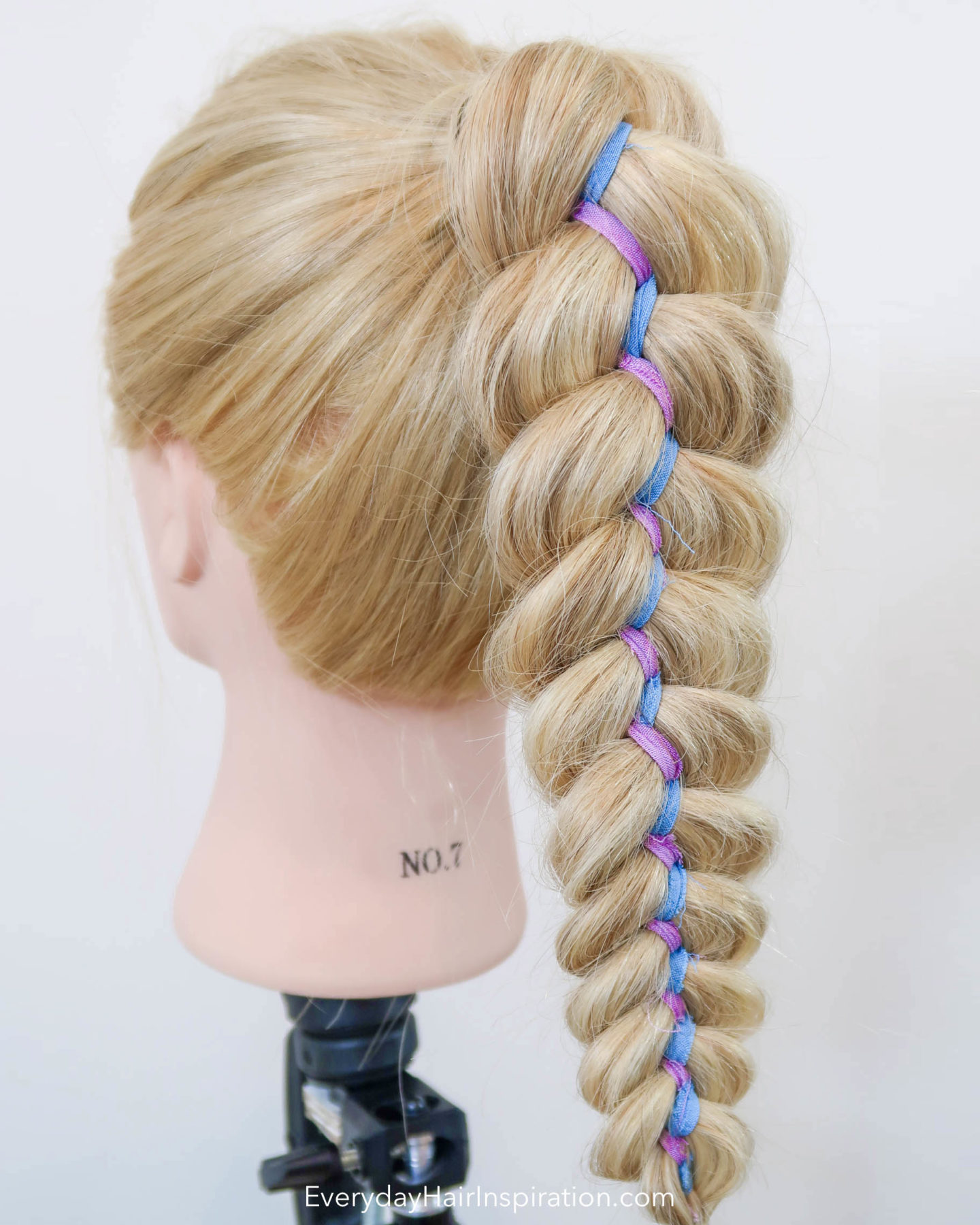 Blonde hairdresser doll with a high ponytail, in which there is a 5 strand ribbon braid, with purple and blue colored ribbon.