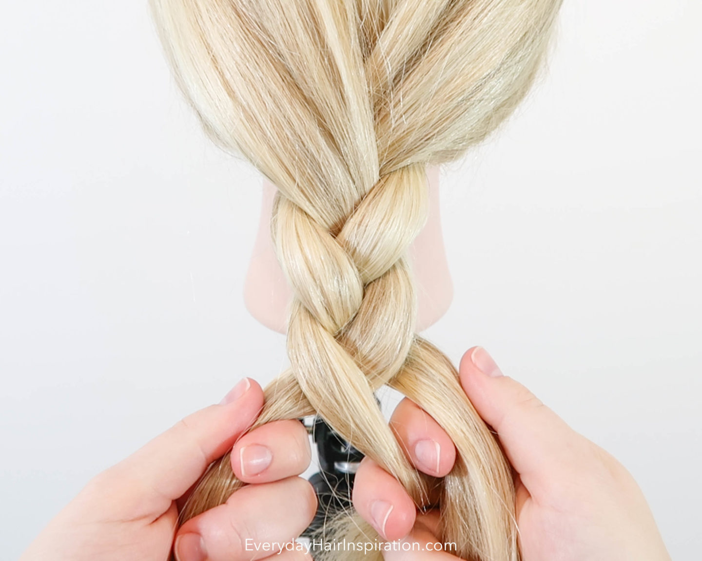 Blonde hairdresser doll with a basic braid getting braided in the hair.