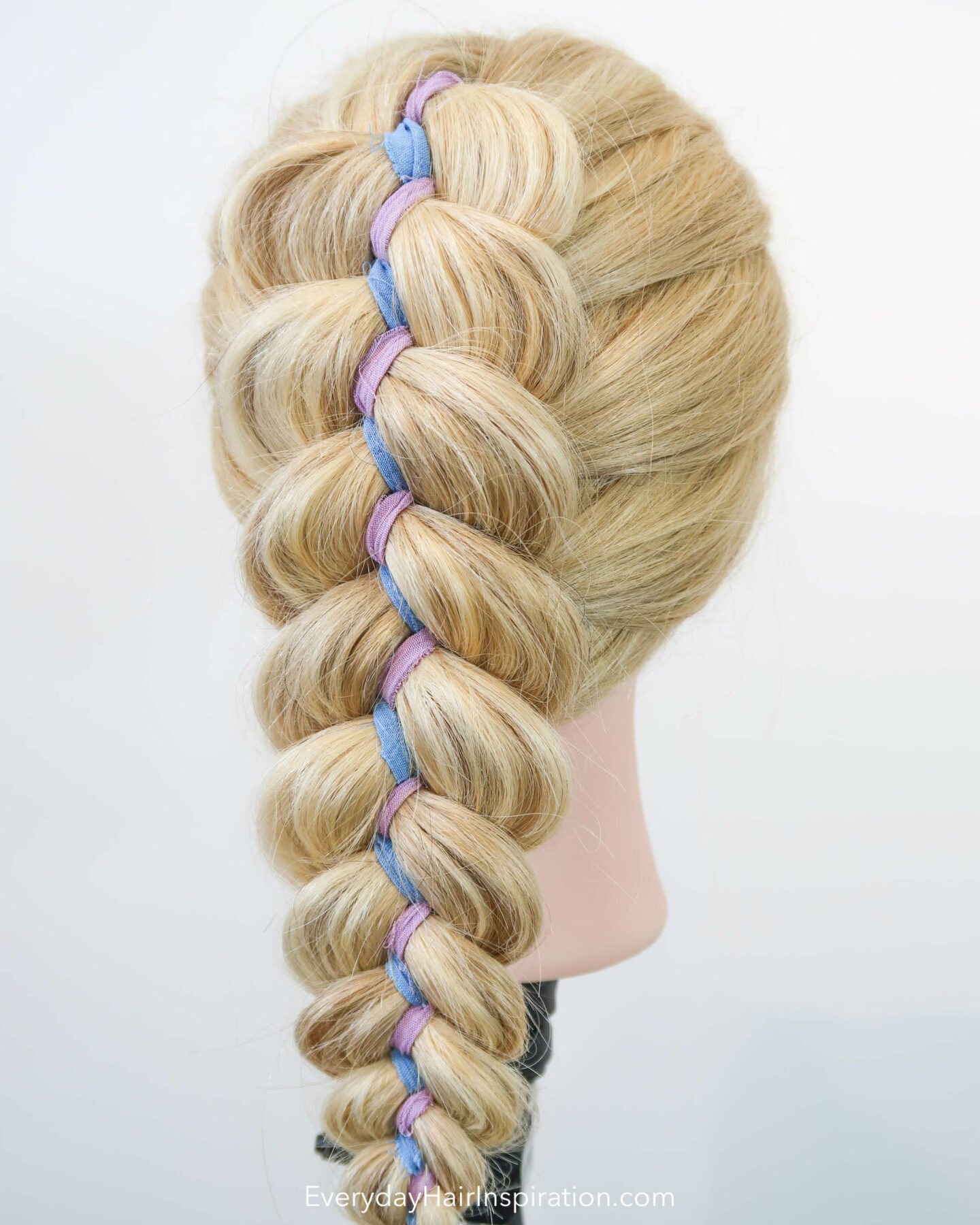Blonde hairdresser doll, seen from the back, at an angle, with a dutch ribbon braid in the hair. The ribbon is blue and purple and is zig zagging down the middle of the braid.