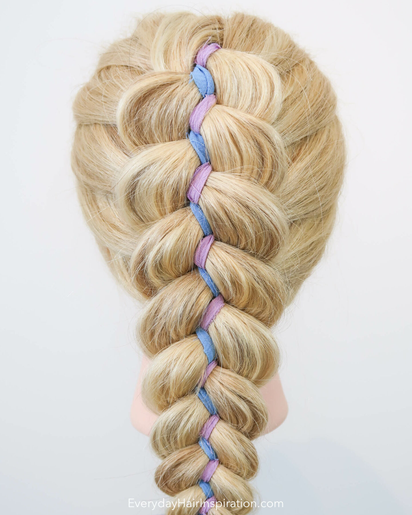 Blonde hairdresser doll, seen from the back with a dutch ribbon braid in the hair. The ribbon is blue and purple and is zig zagging down the middle of the braid.