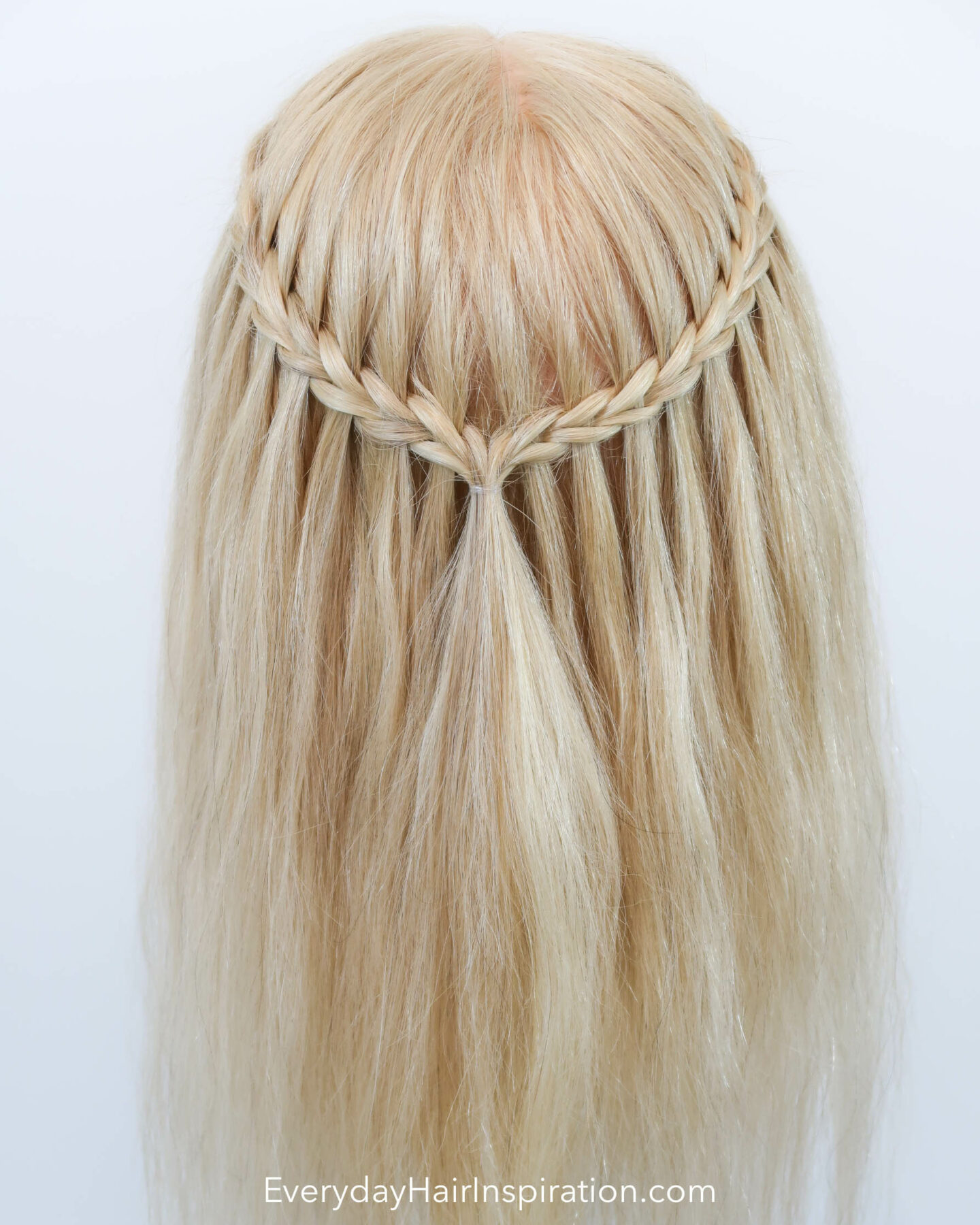 Blonde hairdresser head with a half up half down hair styles with a scissor waterfall braid, seen from the back.