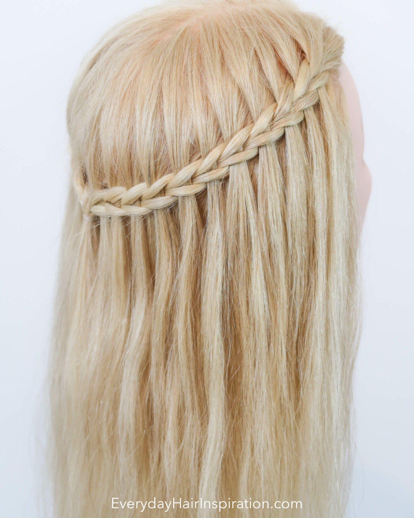 Blonde hairdresser head with a half up half down hair styles with a scissor waterfall braid, seen from the back at an angle.