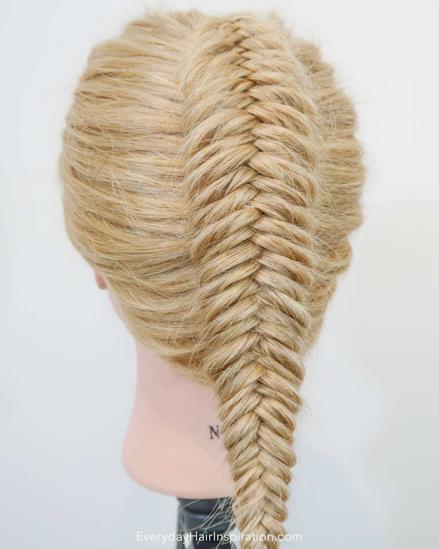 Blonde hairdresser doll seen from the back at an angle, with a single dutch fishtail braid in the hair