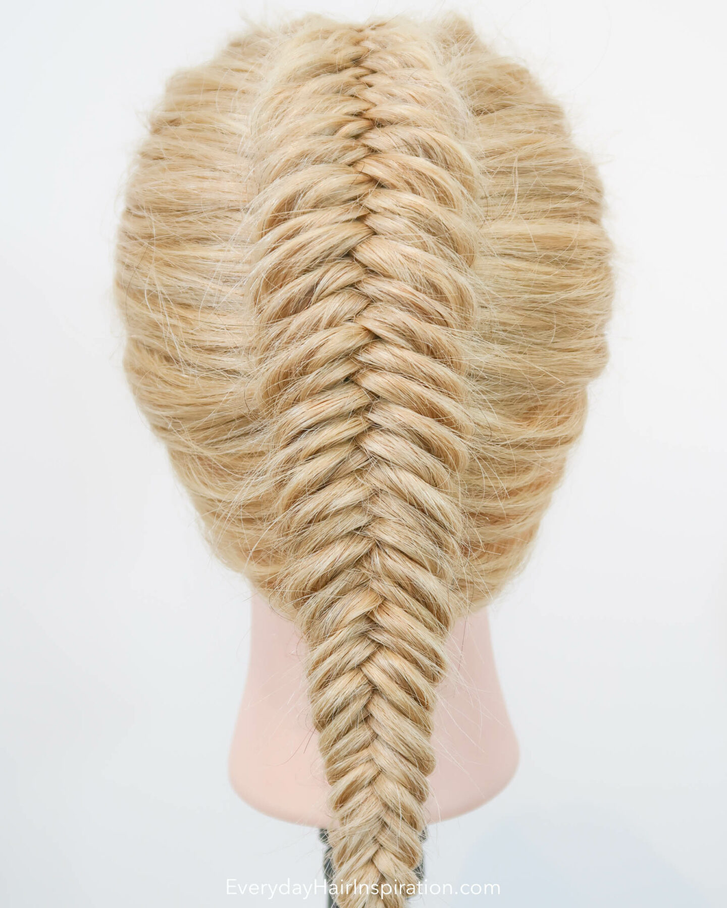 Blonde hairdresser doll seen from the back, with a single dutch fishtail braid in the hair