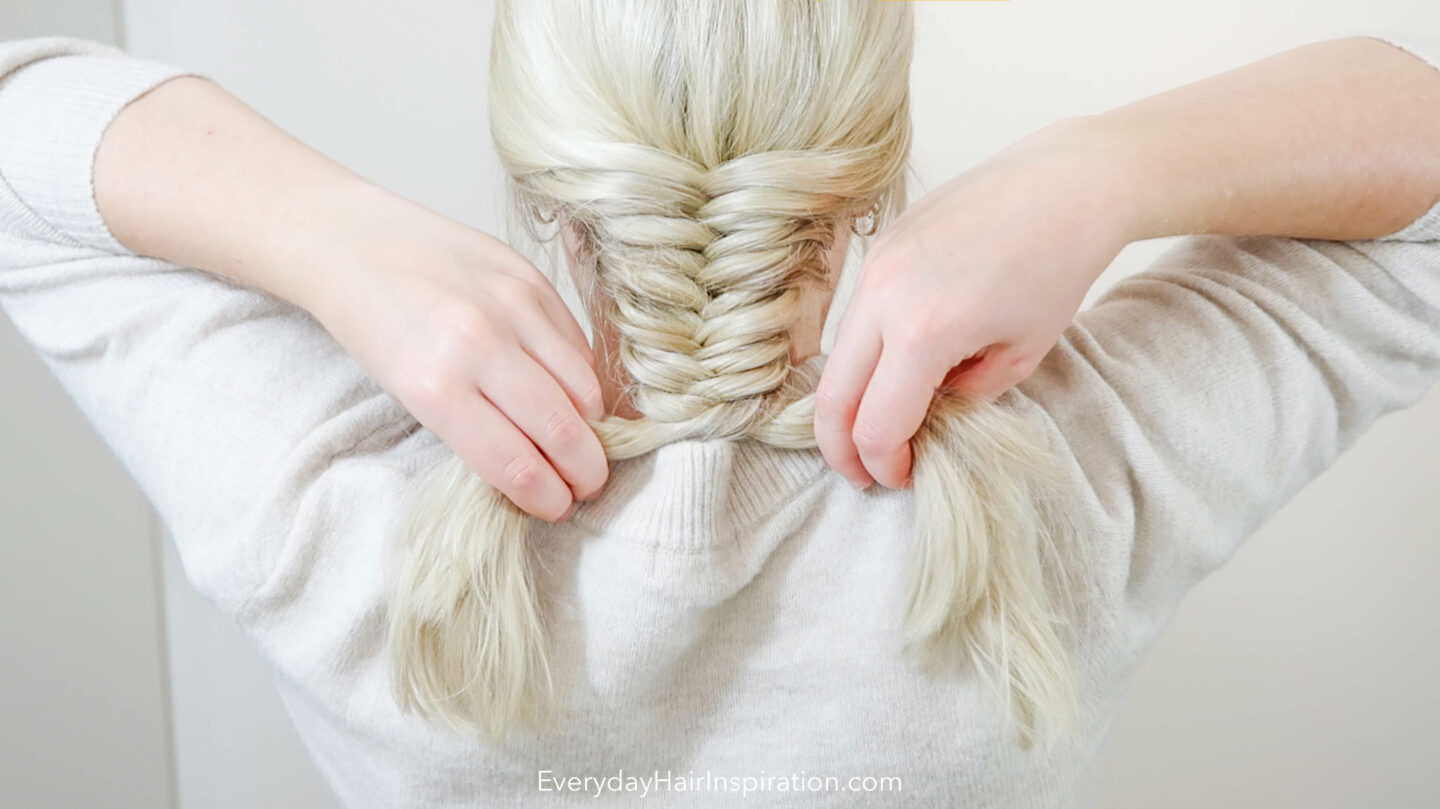 Blonde woman braiding her hair into a fishtail braid down the back of the head.