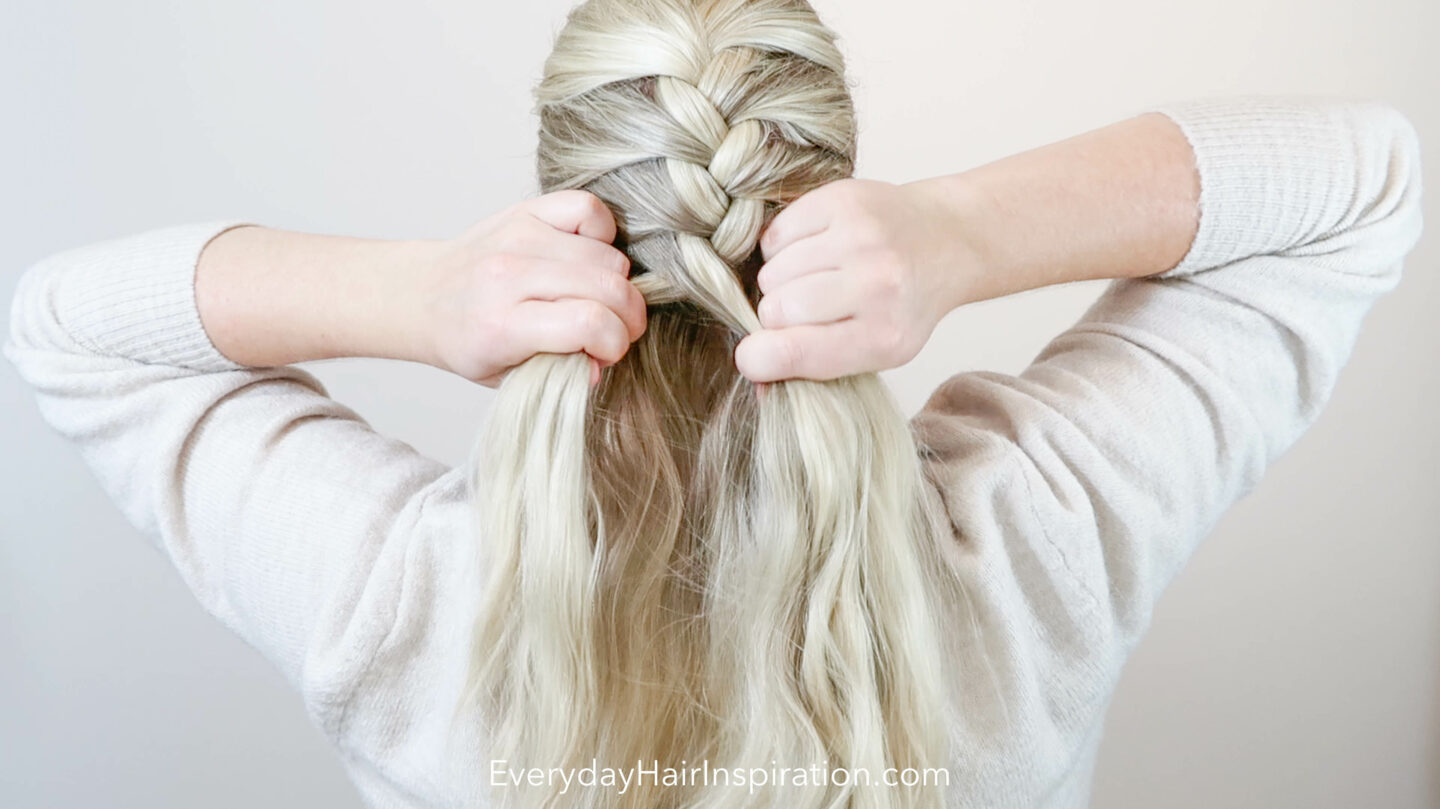 Blonde girl seen from the back braiding a single French braid and she is half way down her head.