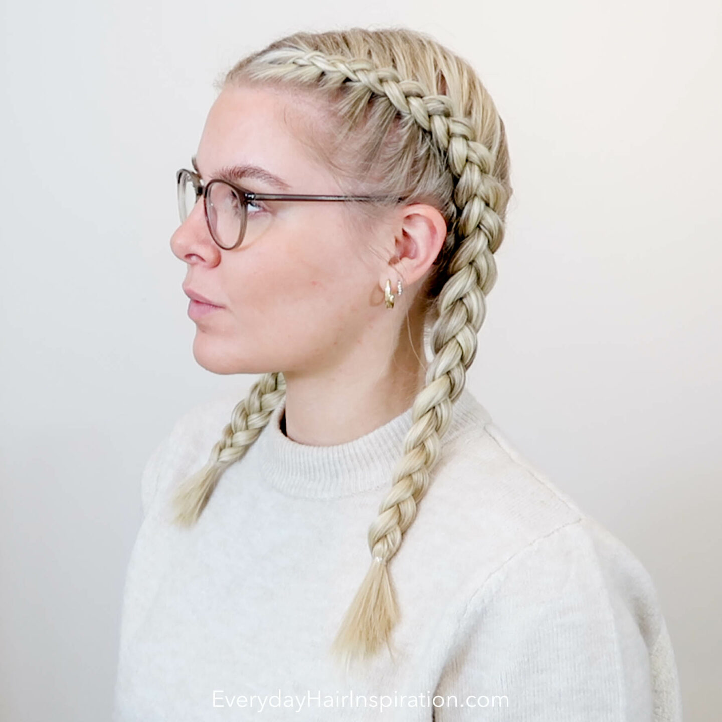 Blonde girl seen from the side with dutch braid in her hair.