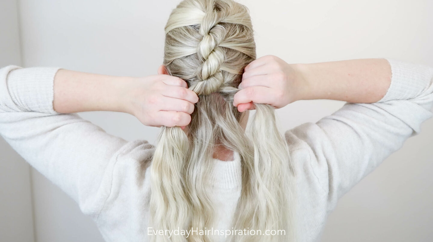 A blonde girls mid way through braiding a single french rope braid down the back of her head.