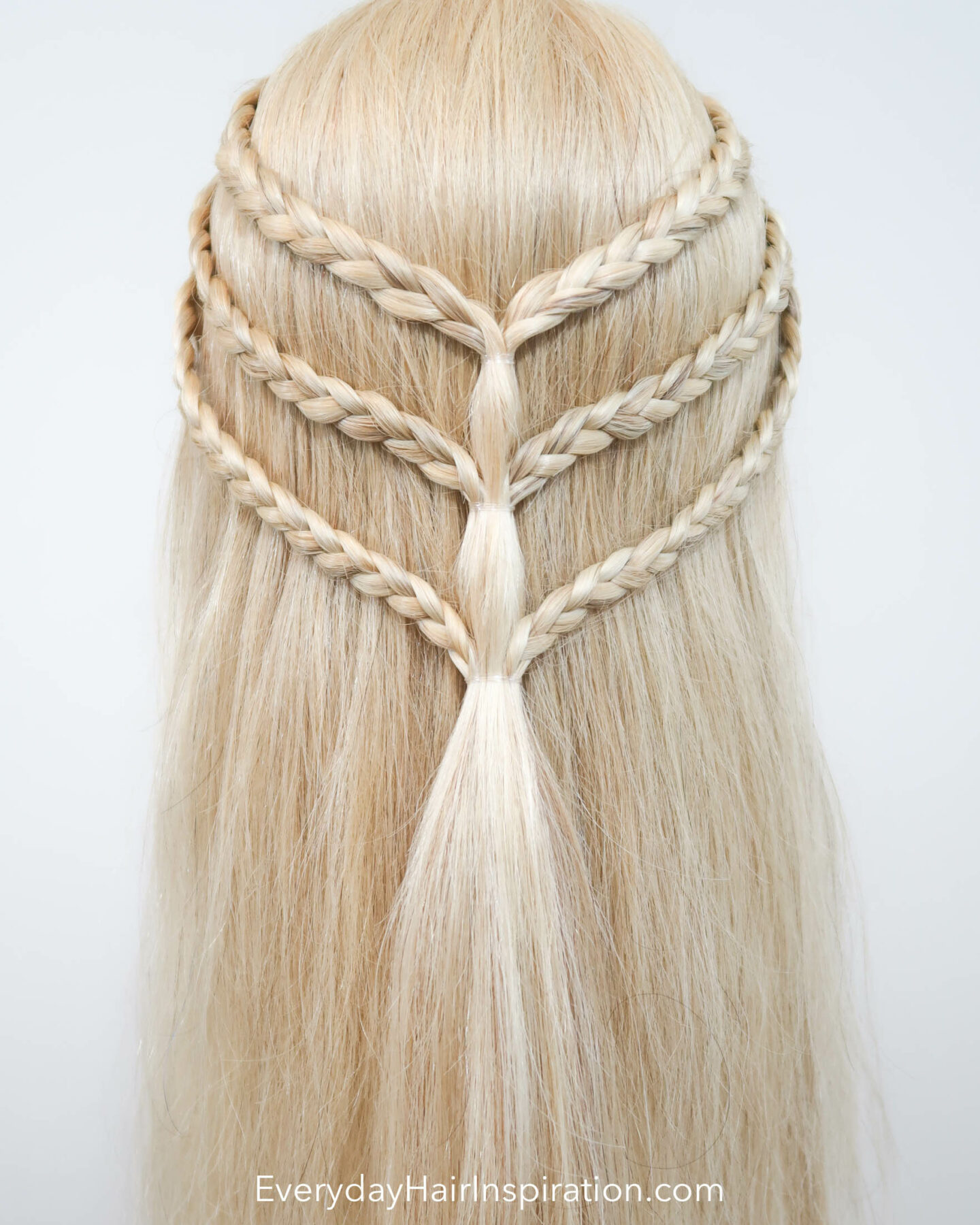 Blonde hairdresser doll with a triple braided half up half down hairstyle seen from the back