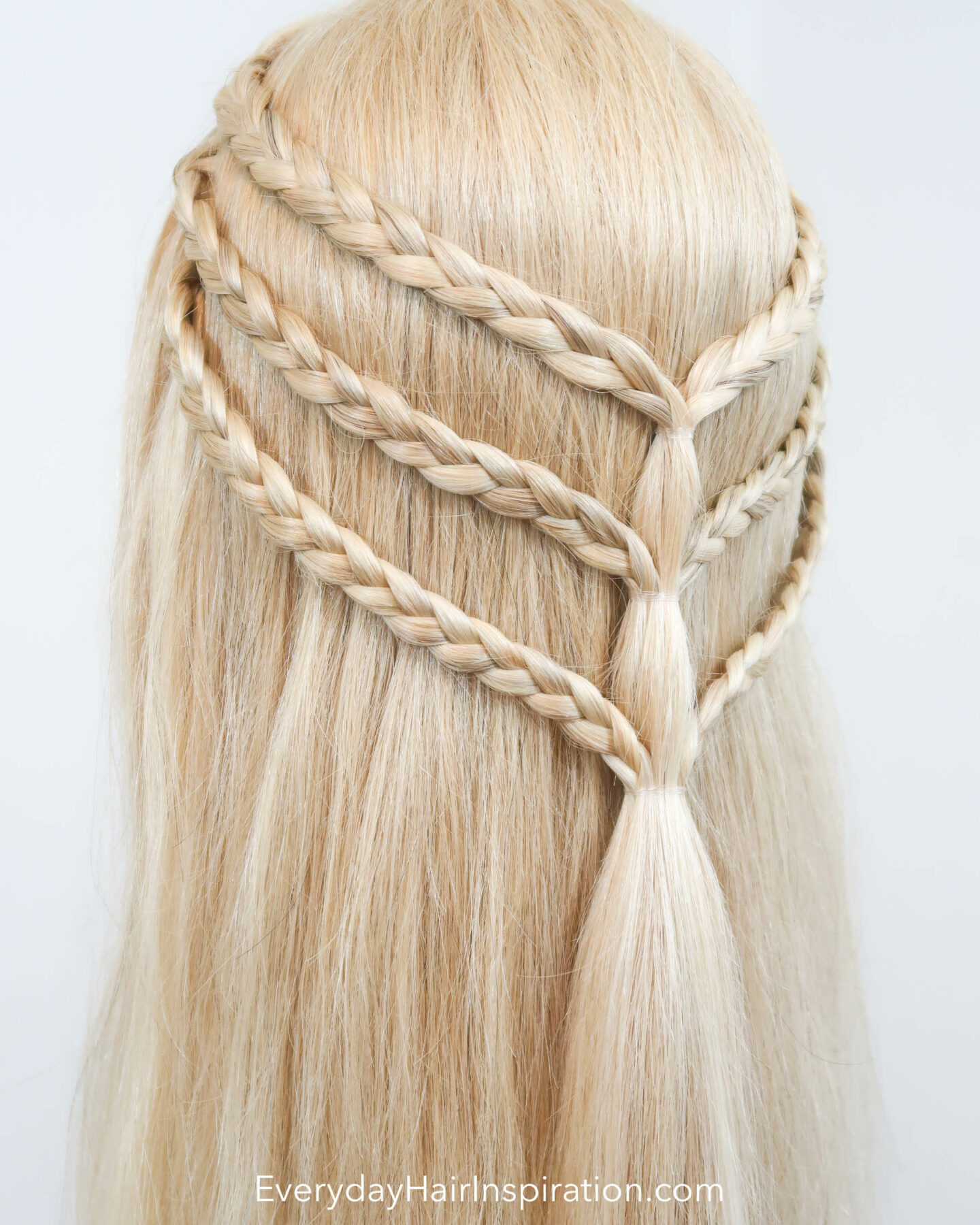 Blonde hairdresser doll with a triple braided half up half down hairstyle seen from the back at an angle