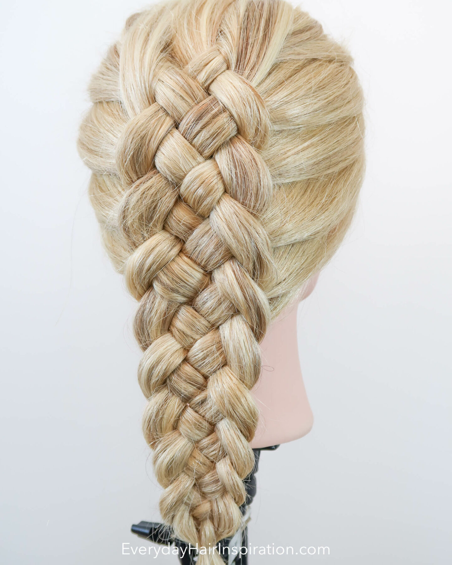 Blonde hairdresser doll with the hair styled into a dutch 5 strand braid, seen from an angle.