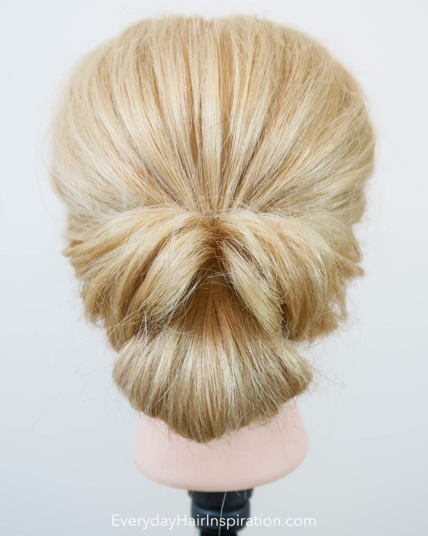 Hairdresser head with a twisted bridal updo, seen from the back.