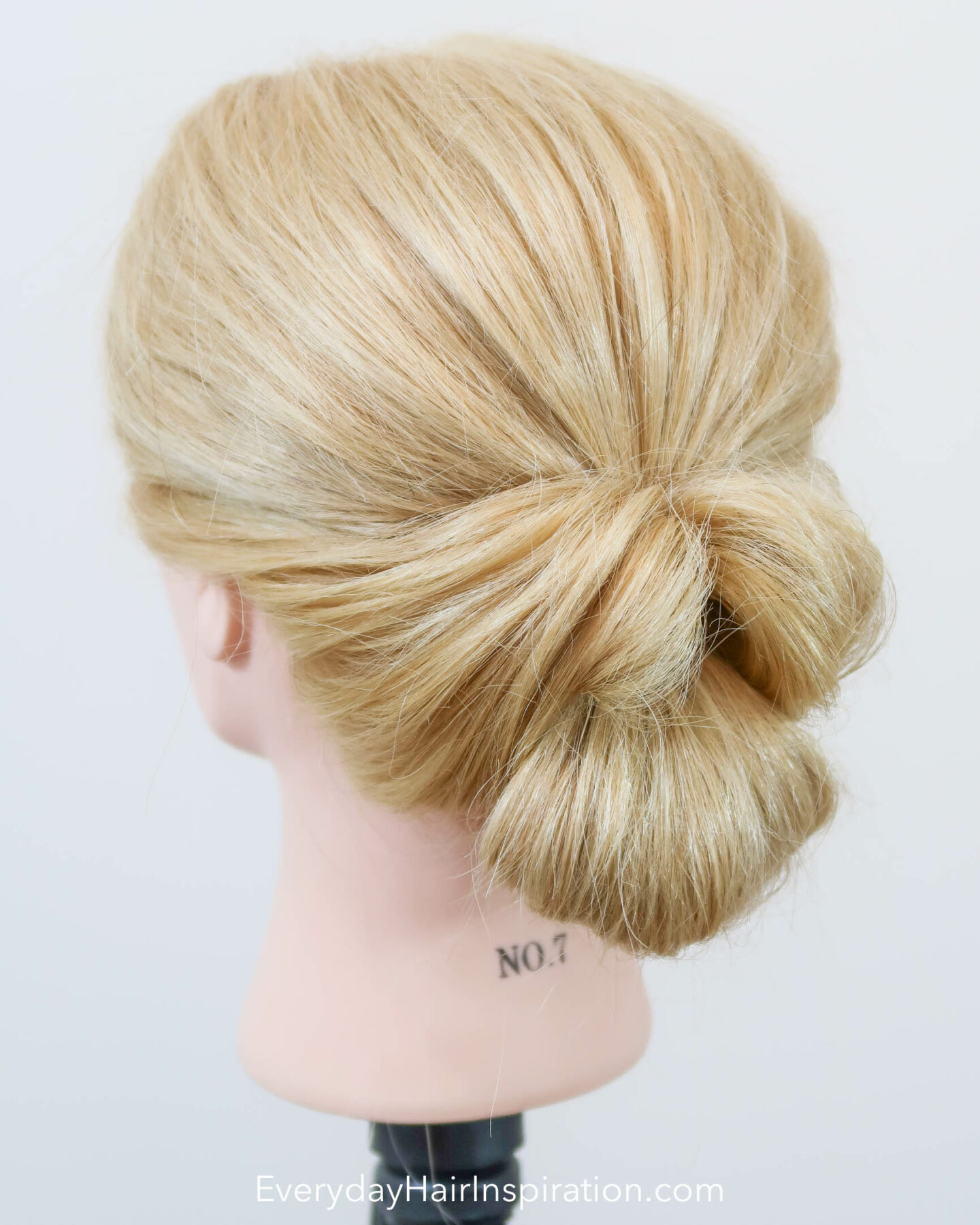 Hairdresser head with a twisted bridal updo, seen from an angle.