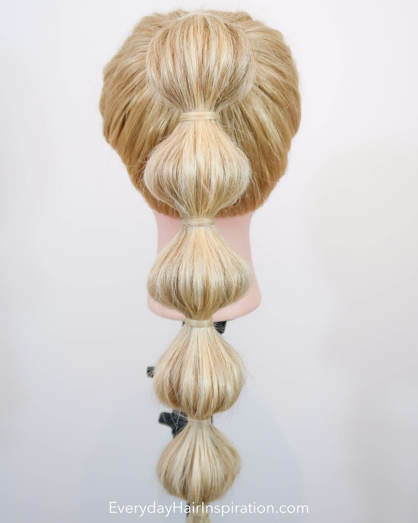 Blonde hairdresser doll, seen from the back with a high ponytail with a bubble braid down the hair.