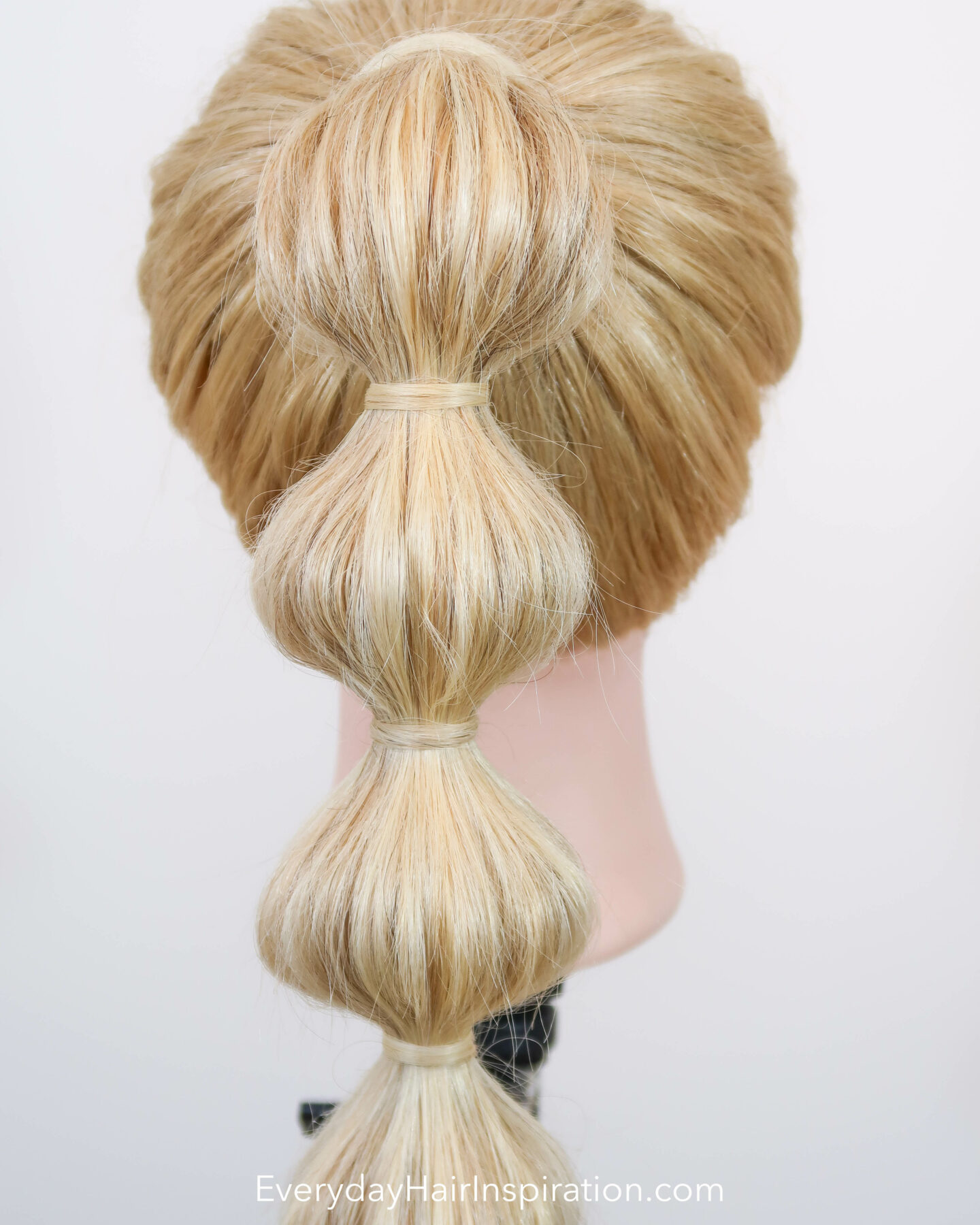 Blonde hairdresser doll, seen from the back with a high ponytail with a bubble braid down the hair. Closeup.
