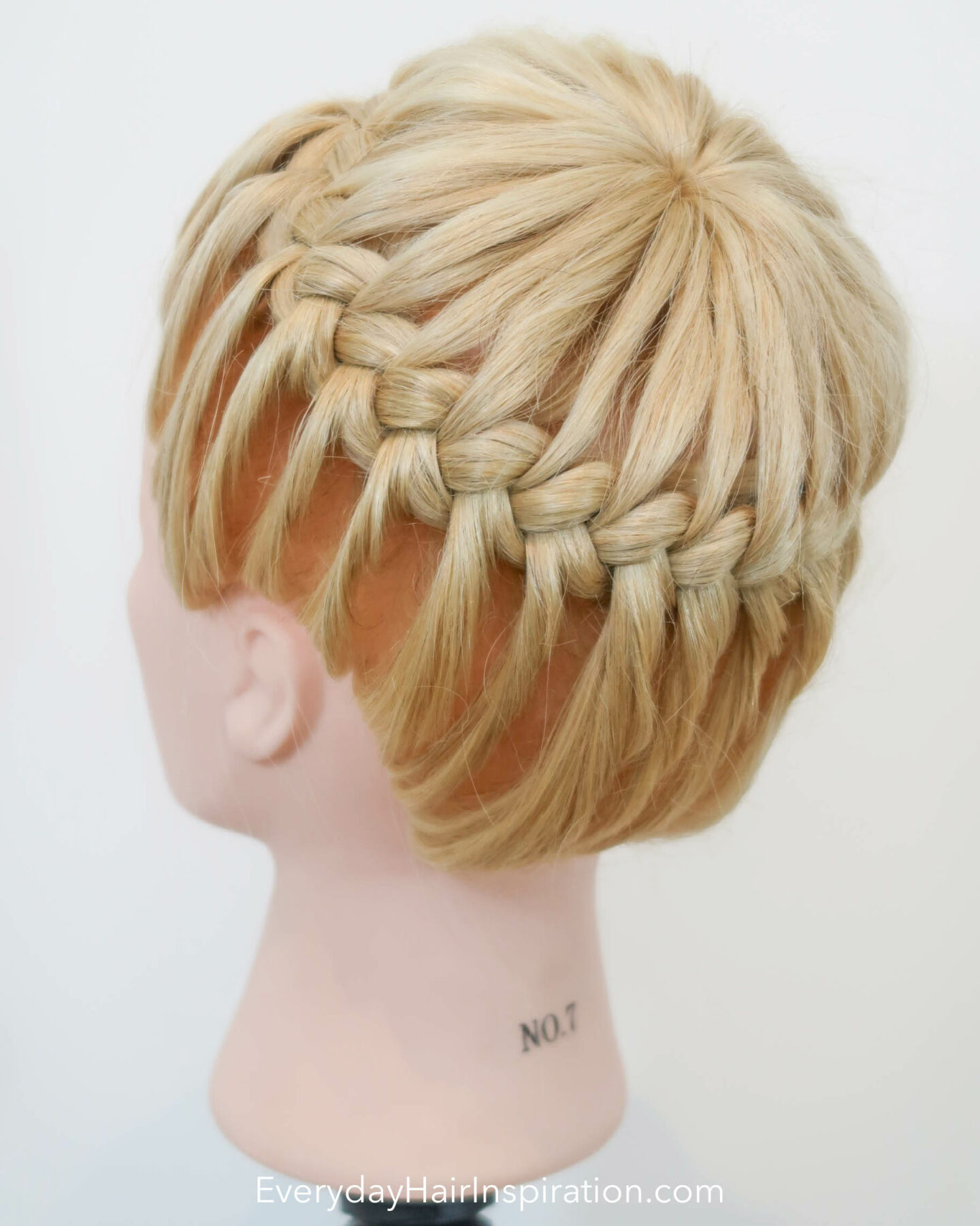 Blonde hairdresser doll seen from the side with a crown braid, braided in the hair.