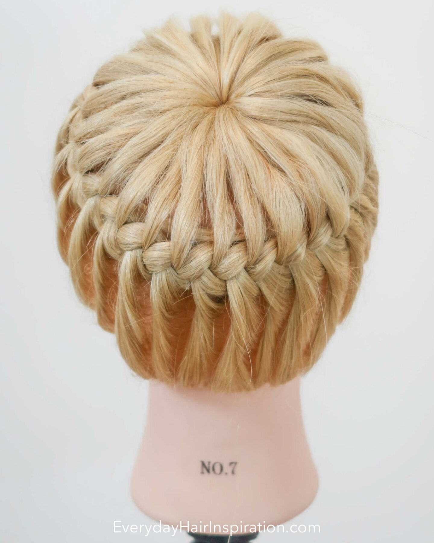Blonde hairdresser doll seen from the back with a crown braid, braided in the hair.