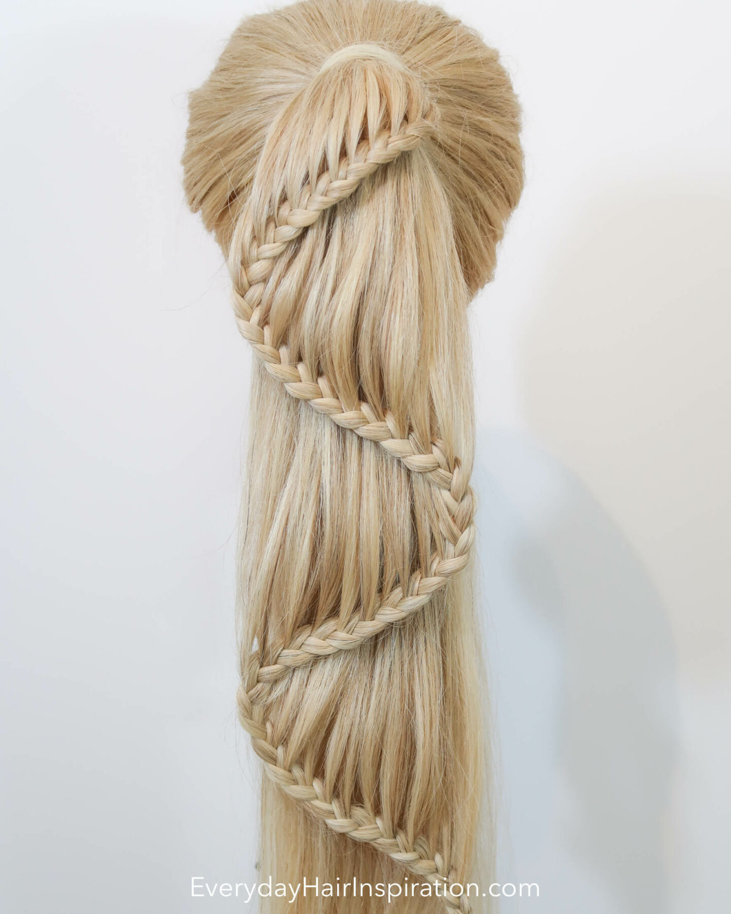 """Blonde hairdresser doll seen from the back with a high ponytail with a braid in the hair. The braid is curving like an """"s"""" shape down the hair."""
