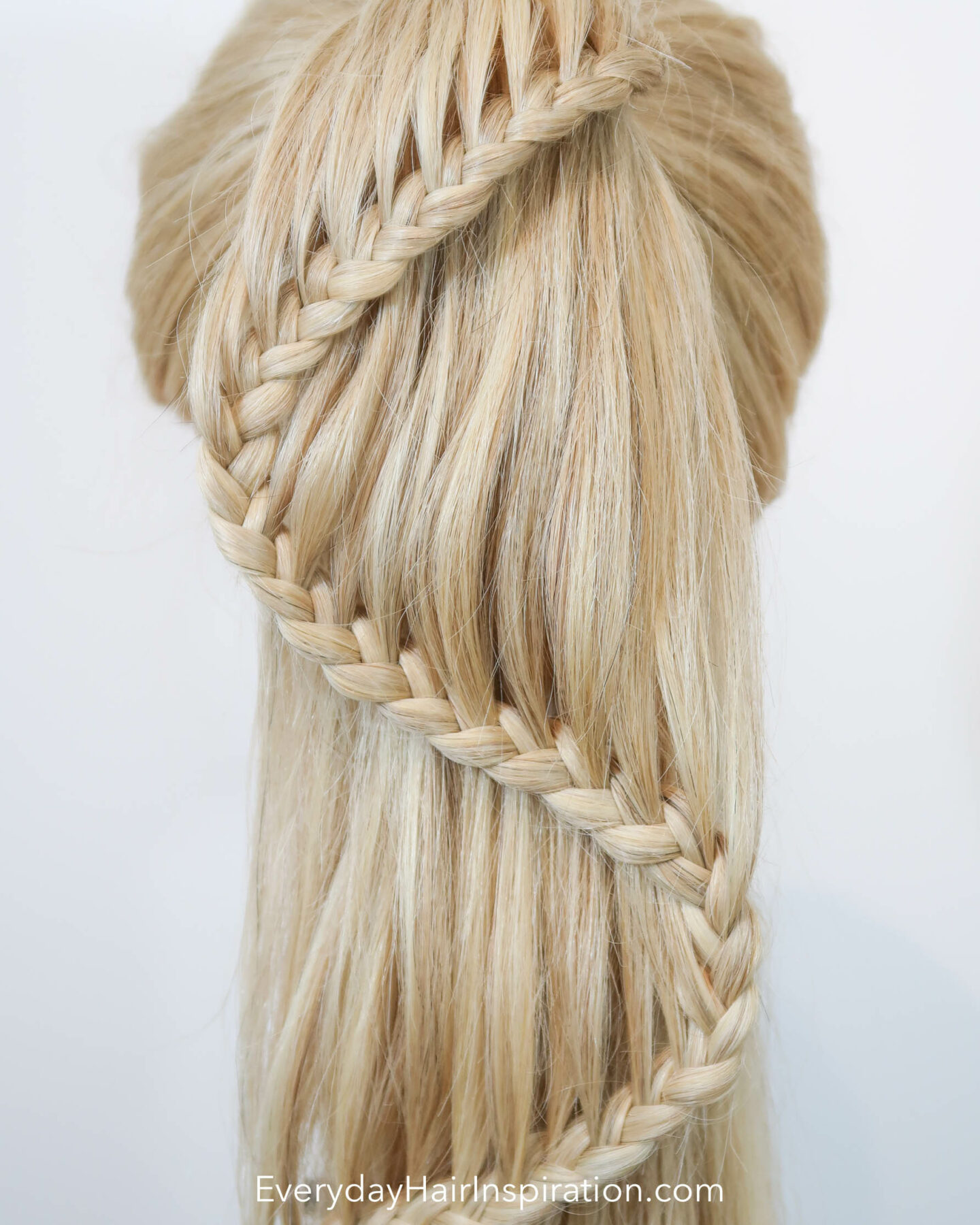 """Blonde hairdresser doll seen from the back with a high ponytail with a braid in the hair. The braid is curving like an """"s"""" shape down the hair - Close up"""