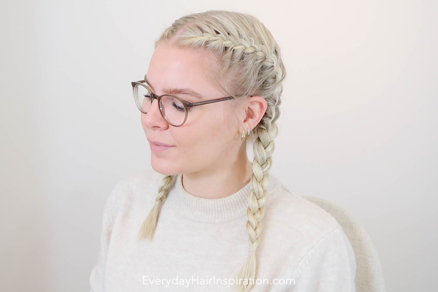 Young blonde woman, sitting in the middle with her head to the side, so you can see the double french braid in her hair.