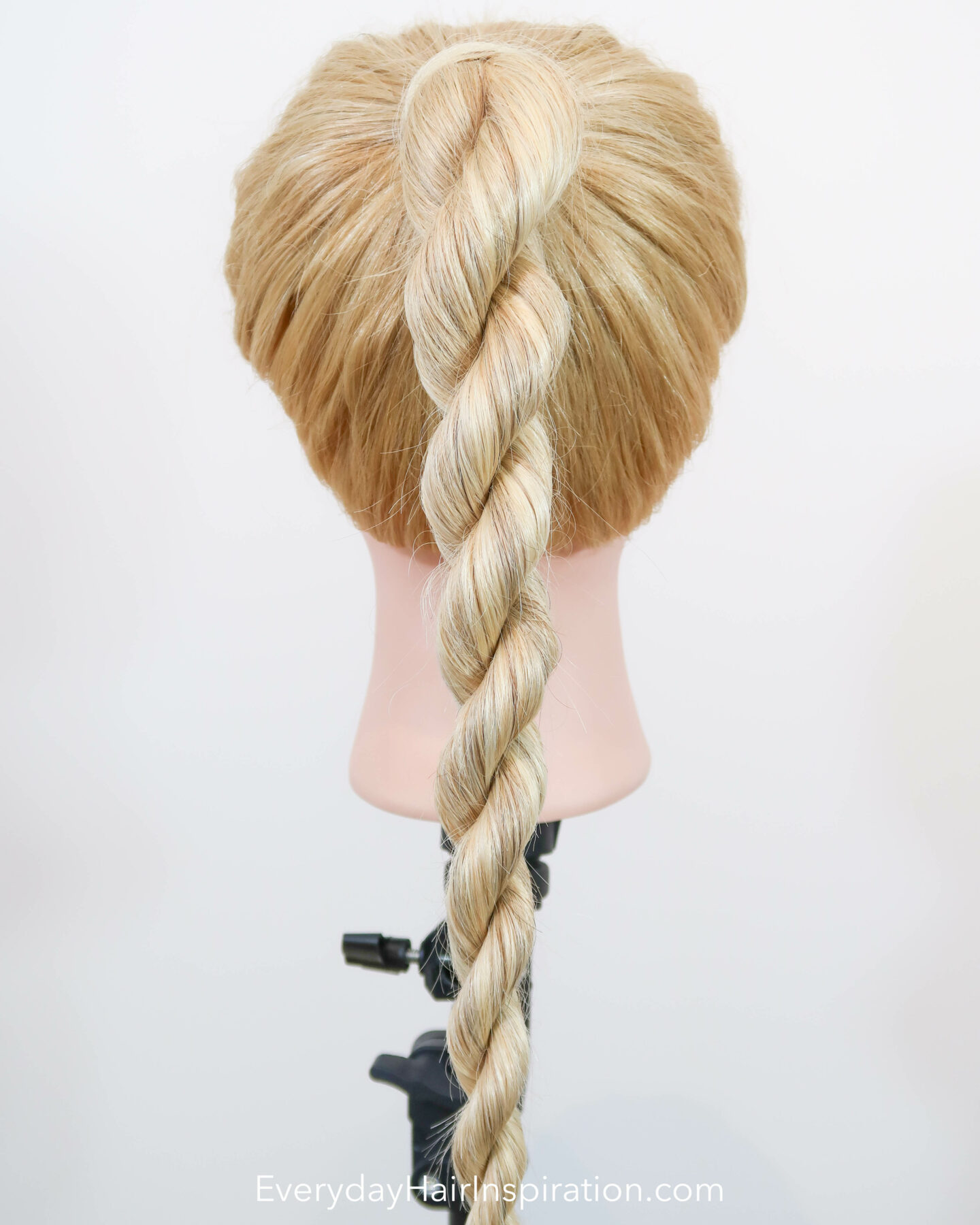 Blonde hairdresser doll seen from the back with a high ponytail with a rope braid, braided in the hair.