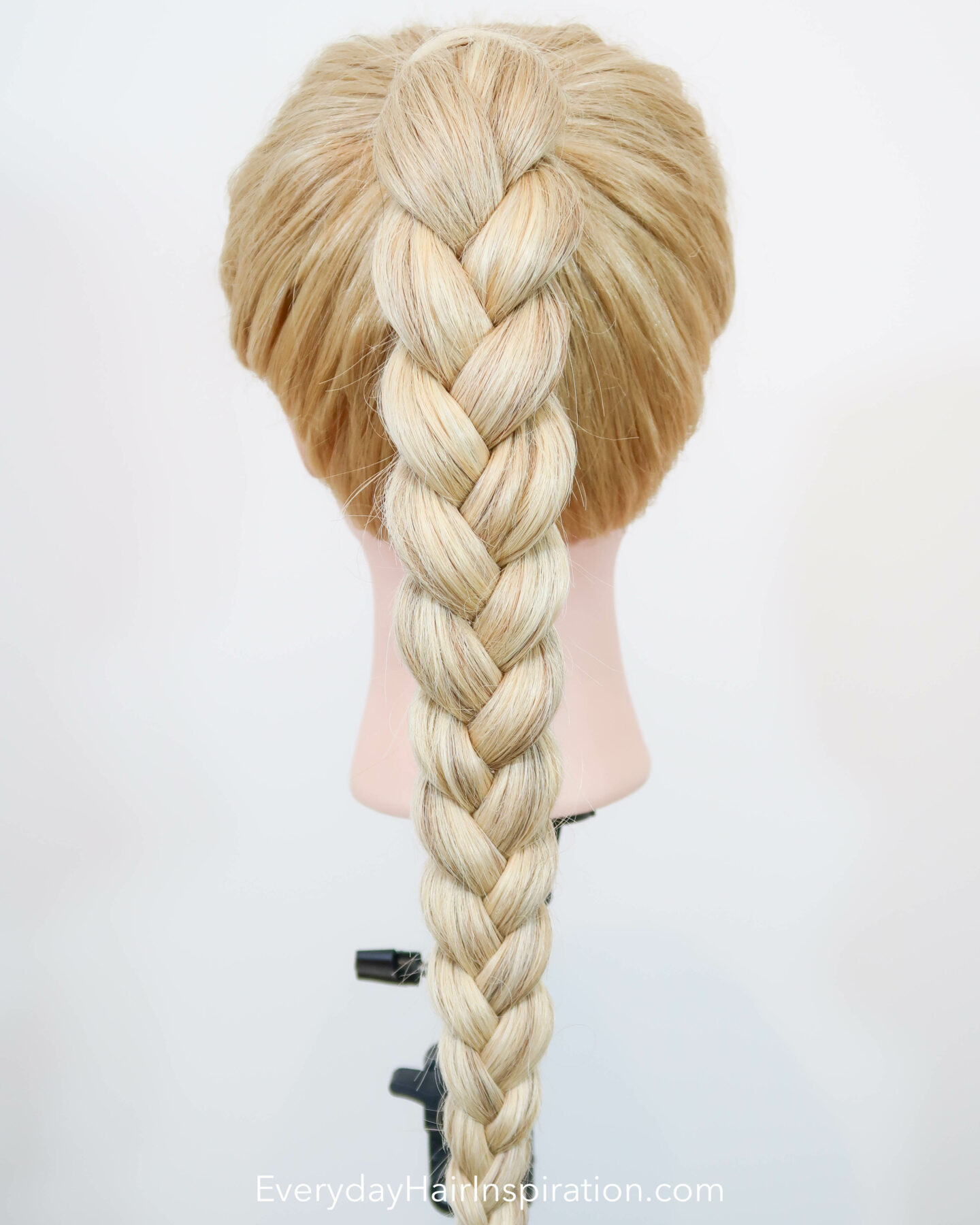 Blonde hairdresser doll seen from the back with a high ponytail with a 3 strand braid, braided in the hair.