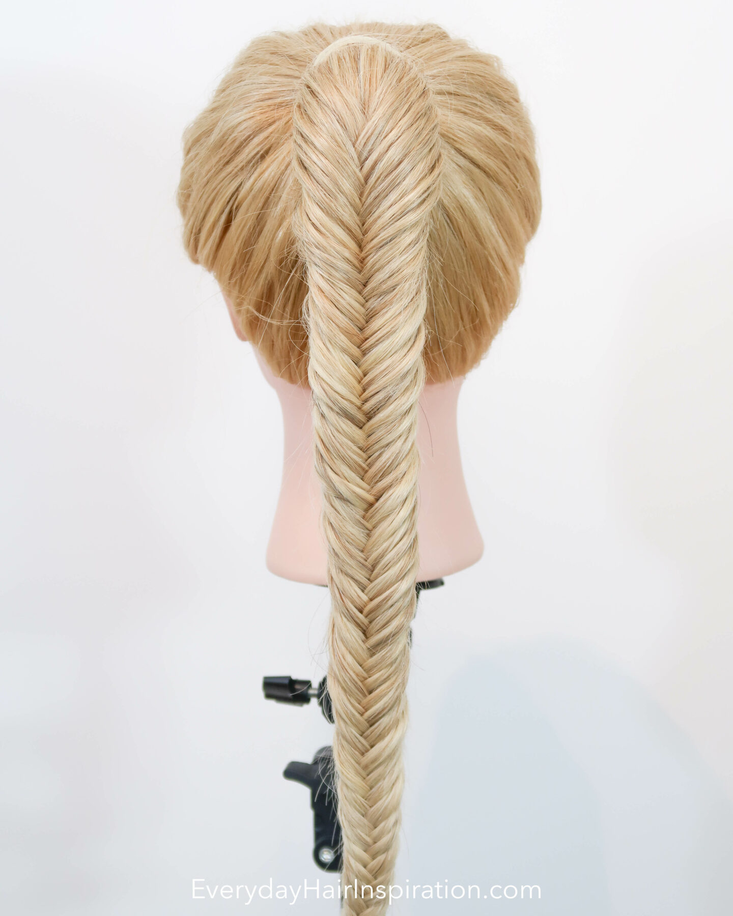 Blonde hairdresser doll seen from the back with a high ponytail with a fishtail braid, braided in the hair.