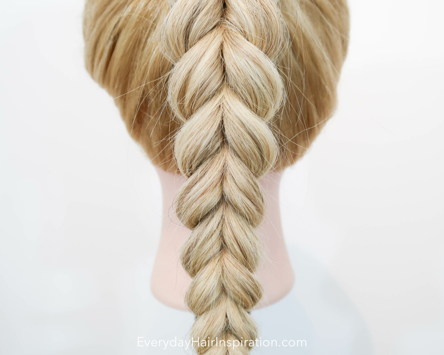 Blonde hairdresser doll seen from the back, close up, with a pull through braid in a high ponytail.
