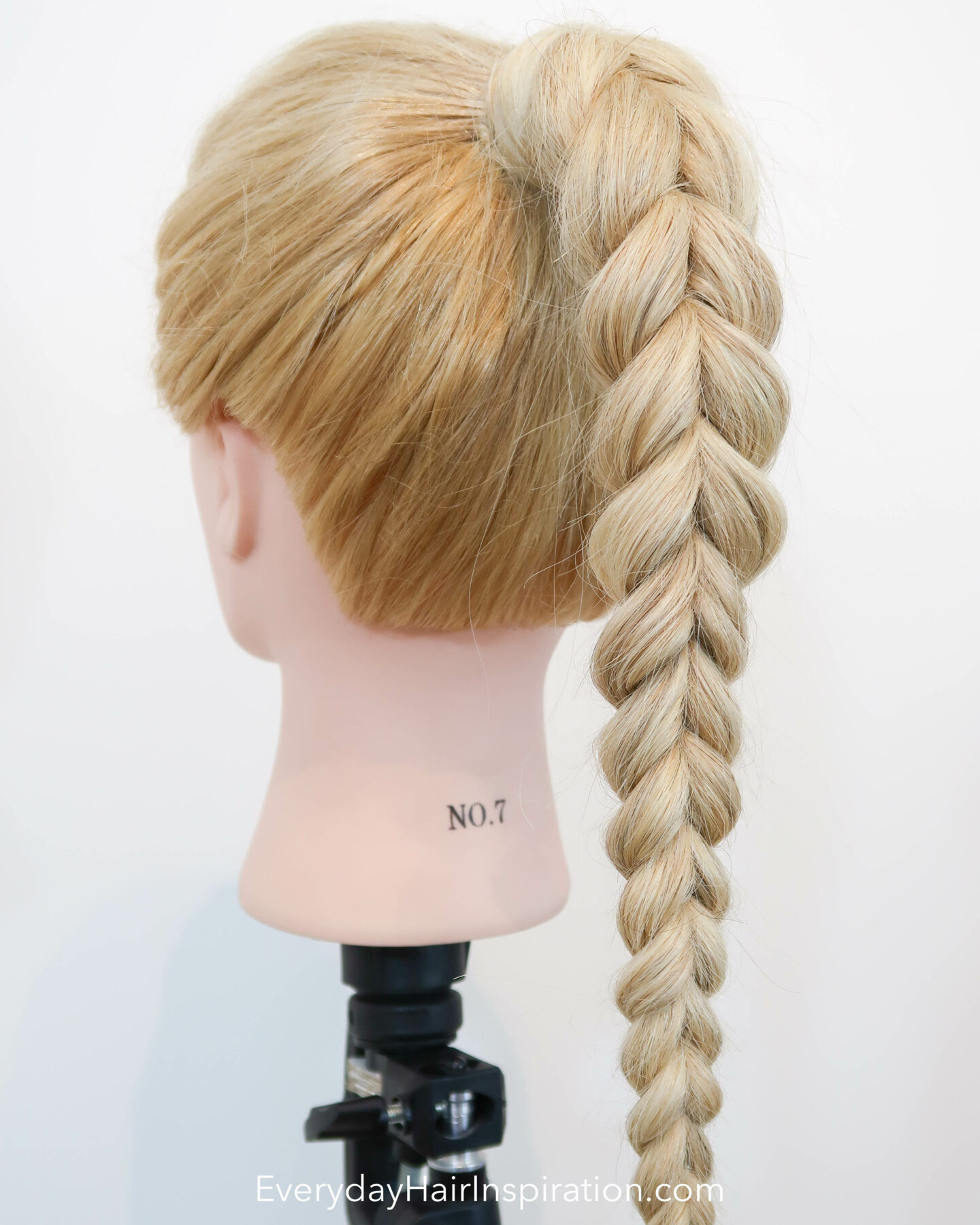 Blonde hairdresser doll seen from the back at an angle with a pull through braid in a high ponytail.