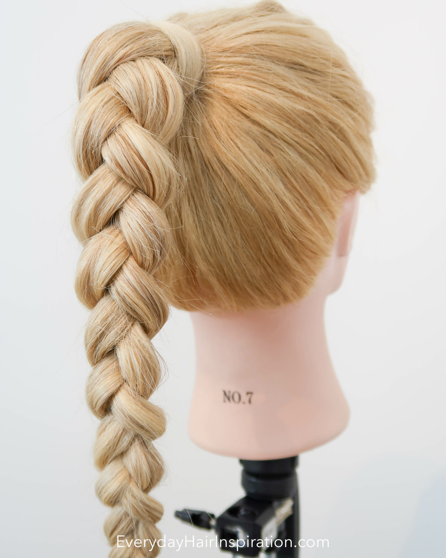 Blonde hairdresser doll seen from the back at an angle, with a high ponytail in the hair, with a 3 strand braid, made out of elastics and no braiding.