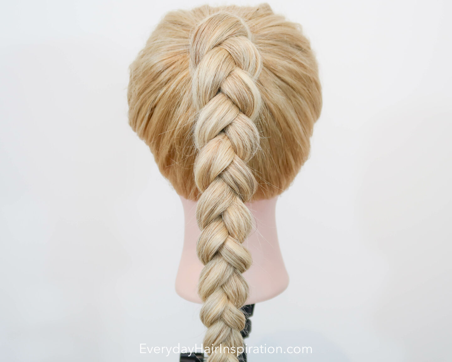 Blonde hairdresser doll seen from the back, with a high ponytail in the hair, with a 3 strand braid, made out of elastics and no braiding.
