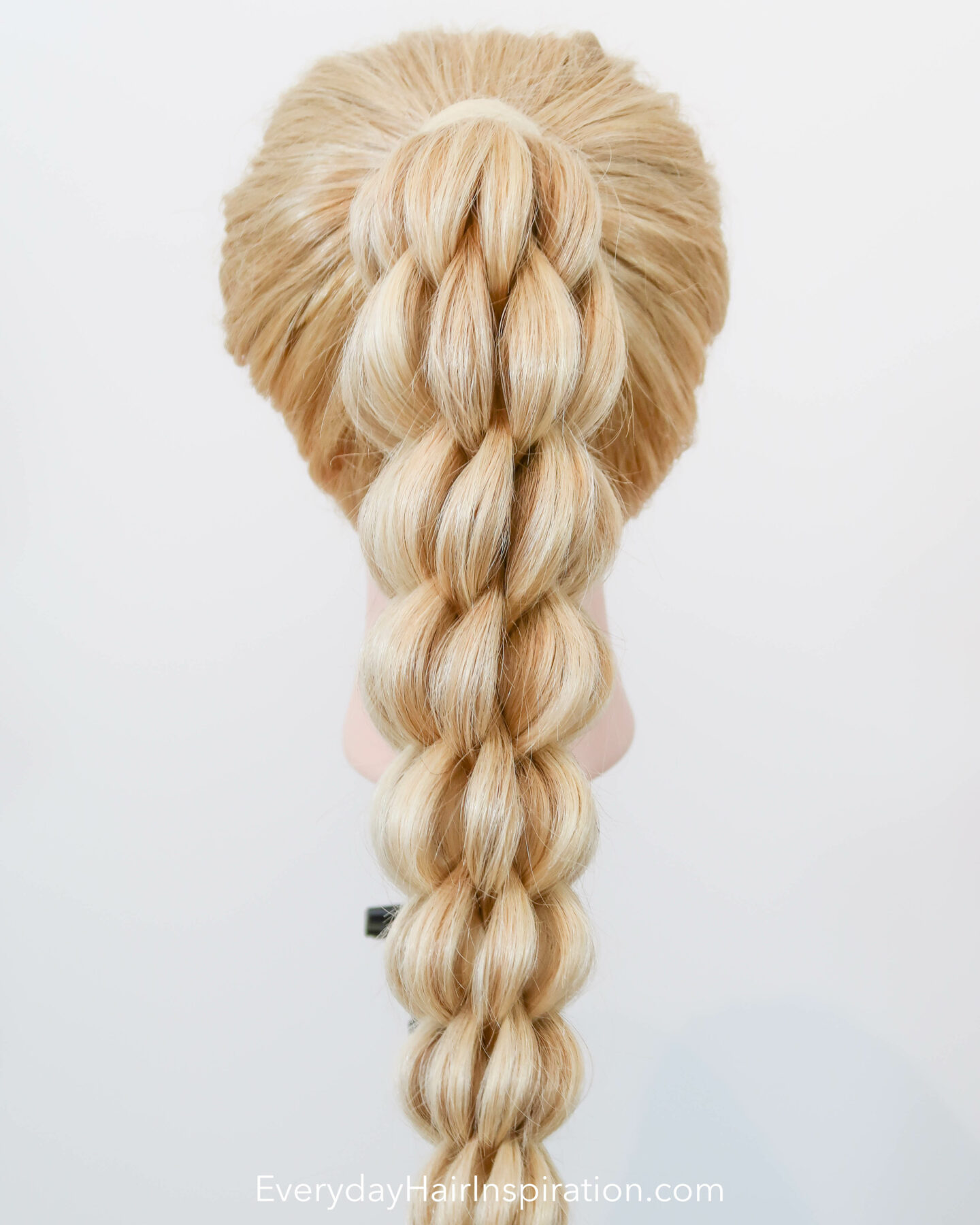 Blonde hairdresser doll seen from the back with a high ponytail in the hair. The ponytail is braided into a 3d pull through braid.