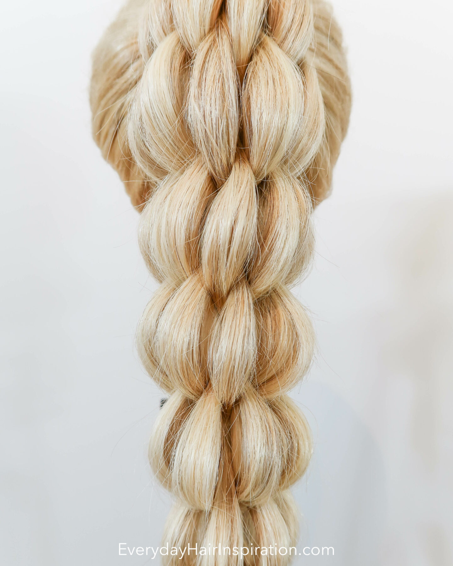 Blonde hairdresser doll seen from the back with a high ponytail in the hair. The ponytail is braided into a 3d pull through braid. Closeup of the hair.