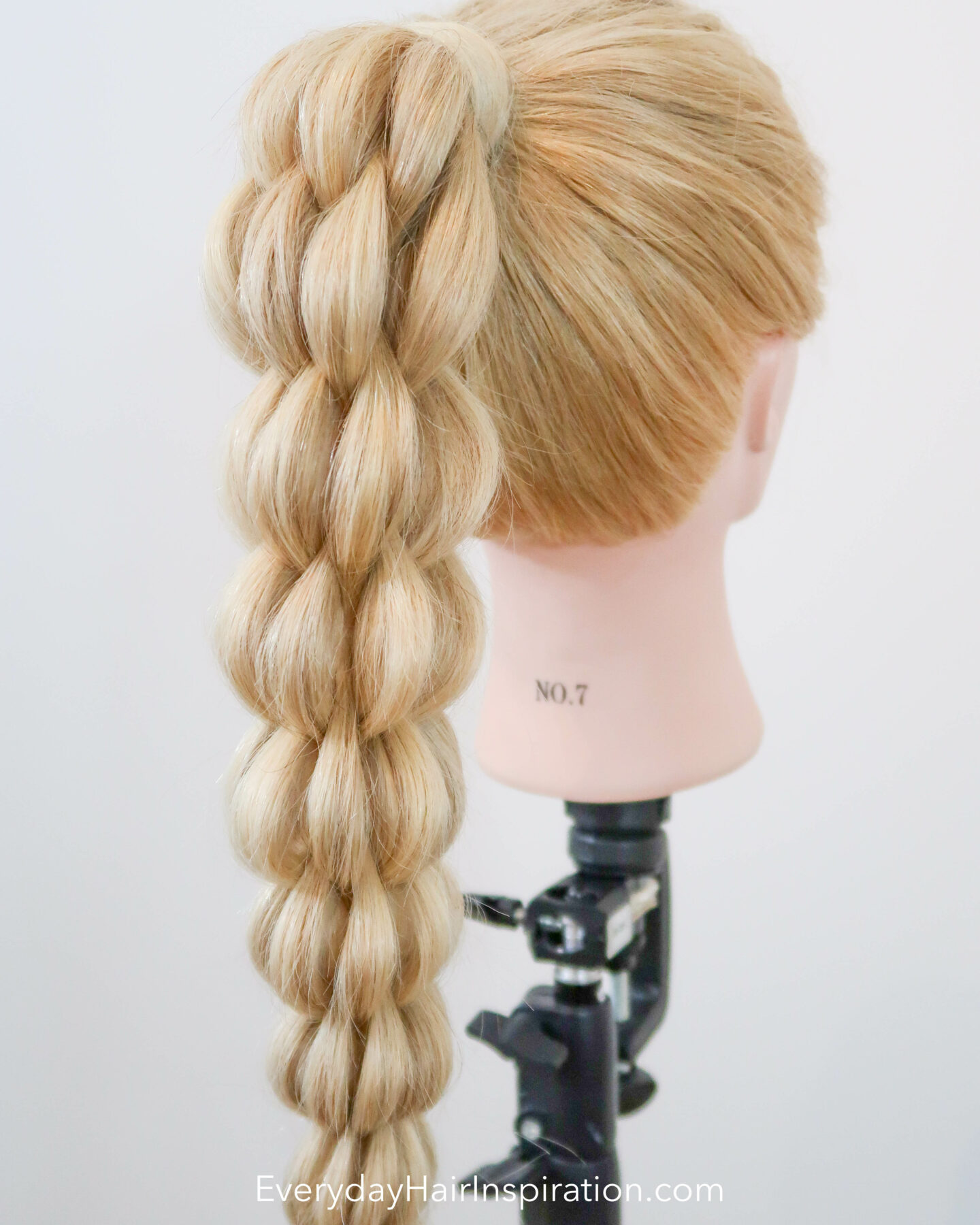 Blonde hairdresser doll seen from the back at an angle with a high ponytail in the hair. The ponytail is braided into a 3d pull through braid.