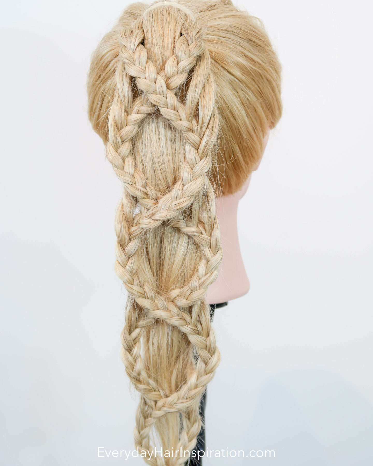 Blonde hair dresser doll seen dorm the back at an angle with a criss-cross braided ponytail.