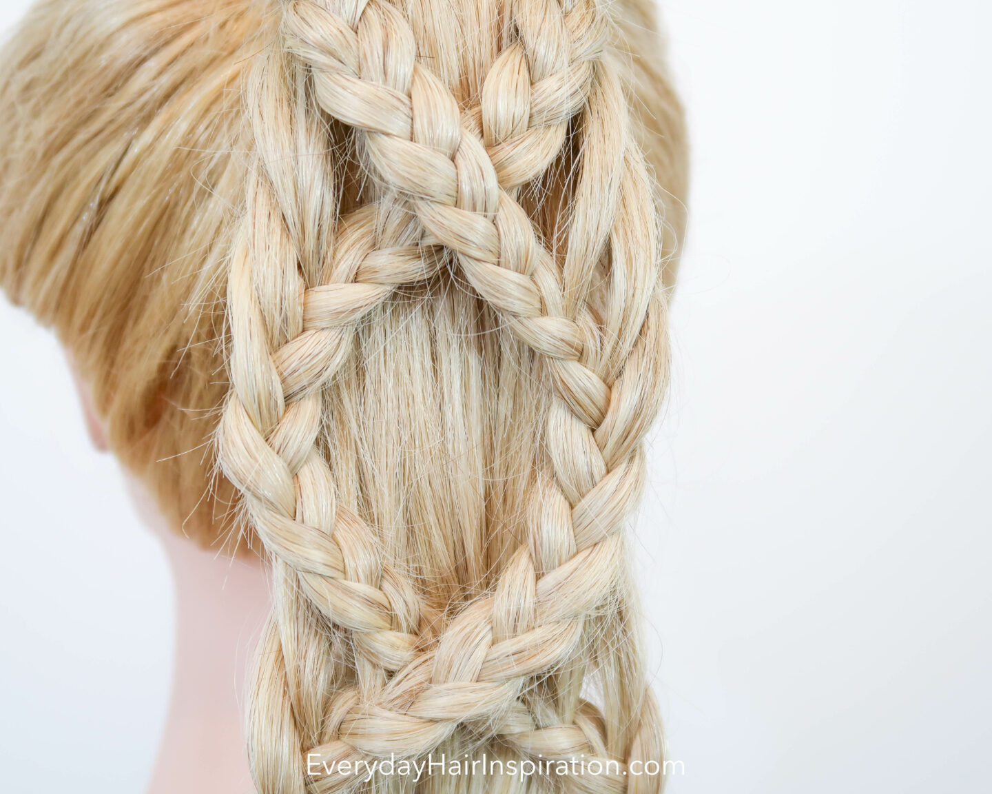 Blonde hair dresser doll seen dorm the back, close up, with a criss-cross braided ponytail.