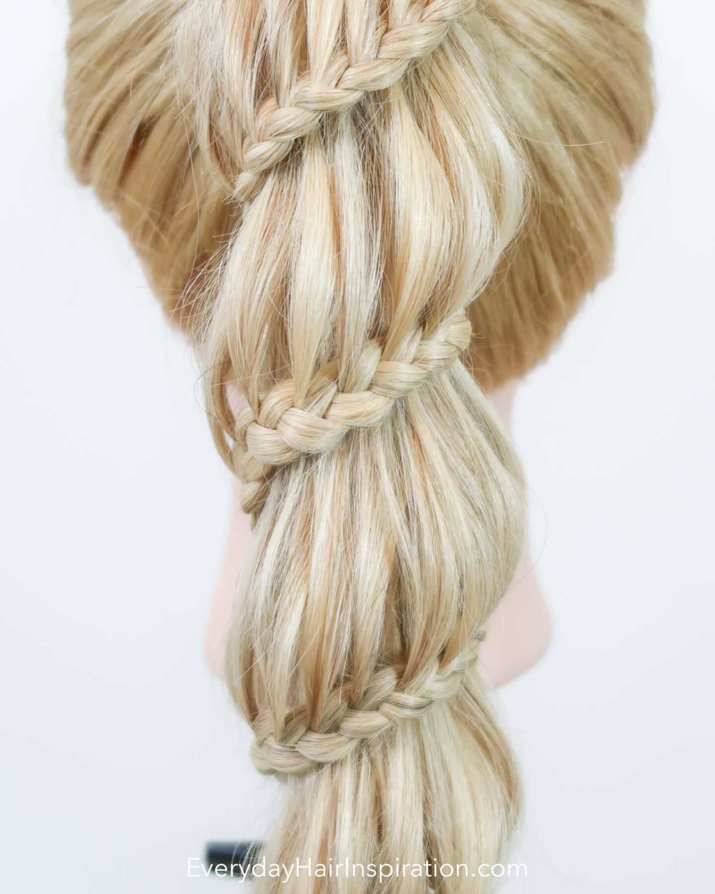 Blonde hairdresser doll seen from the back with a high ponytail. The ponytail is braided into a spiral braid, the wraps around the ponytail all the way down. Closeup of the braid.