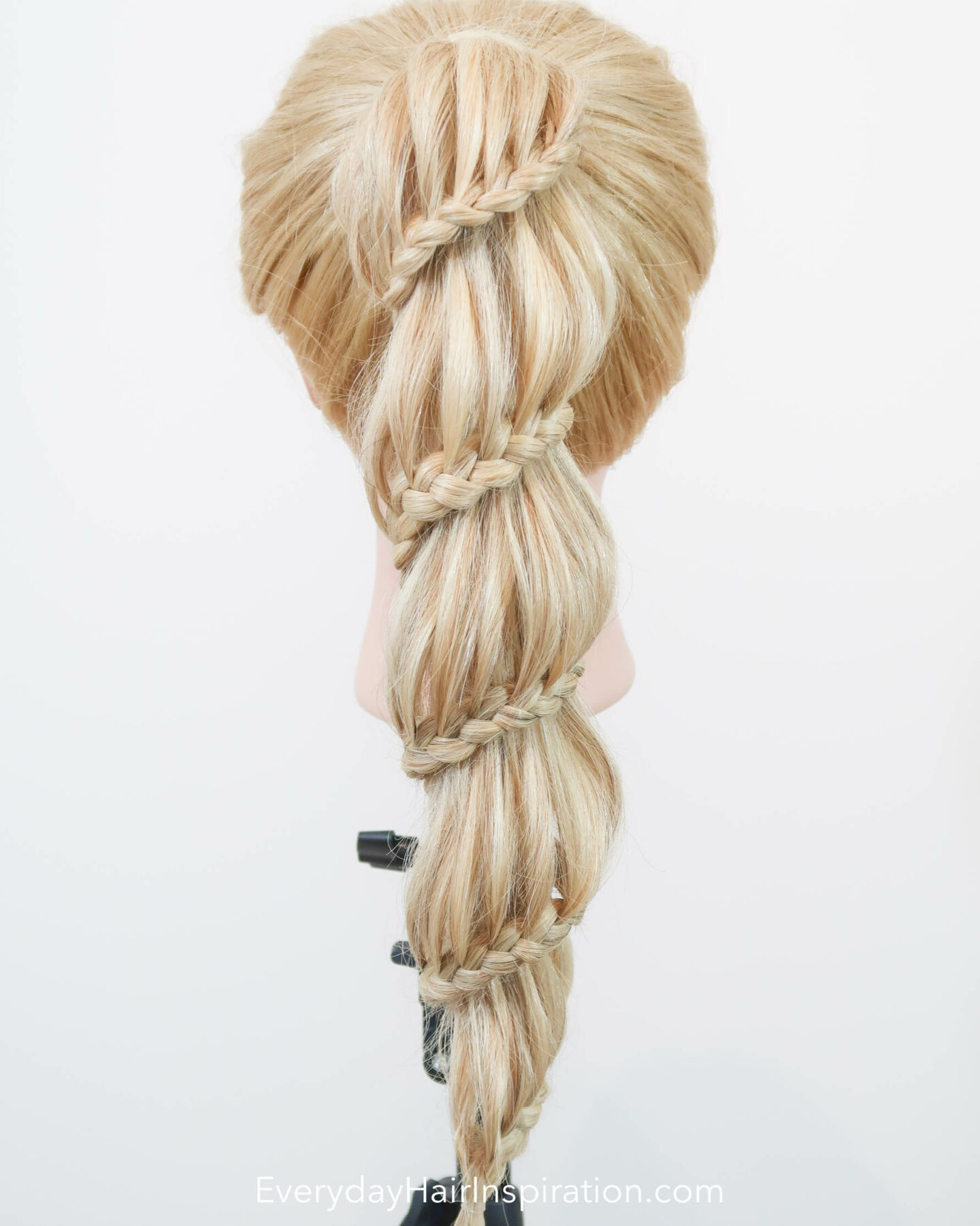 Blonde hairdresser doll seen from the back with a high ponytail. The ponytail is braided into a spiral braid, the wraps around the ponytail all the way down.