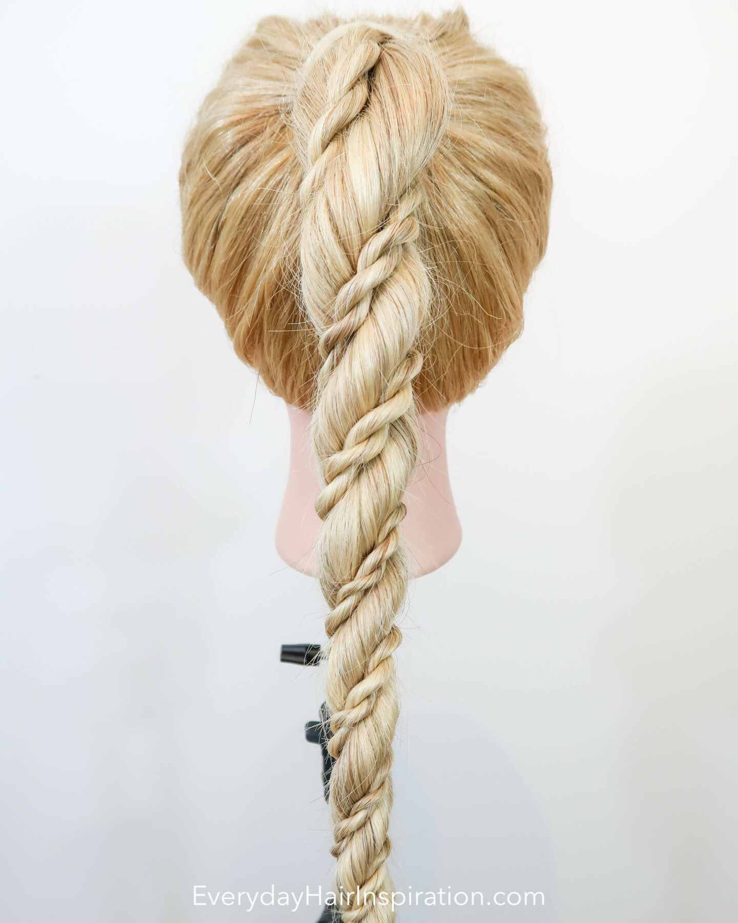 Blonde hairdresser doll seen from the back, with a high ponytail in the hair. The ponytail is a rope braid, with 2 small rope braids wrapped around the big rope braid.