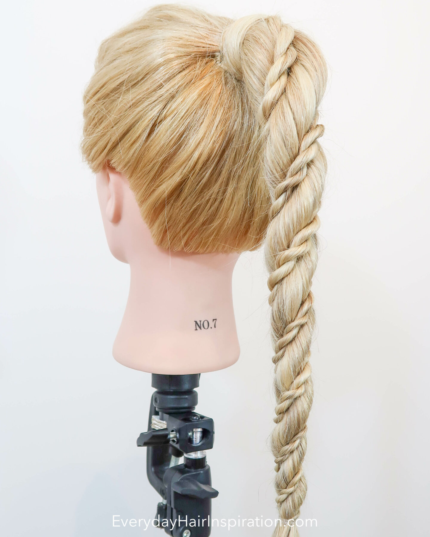 Blonde hairdresser doll seen from an angle, with a high ponytail in the hair. The ponytail is a rope braid, with 2 small rope braids wrapped around the big rope braid.