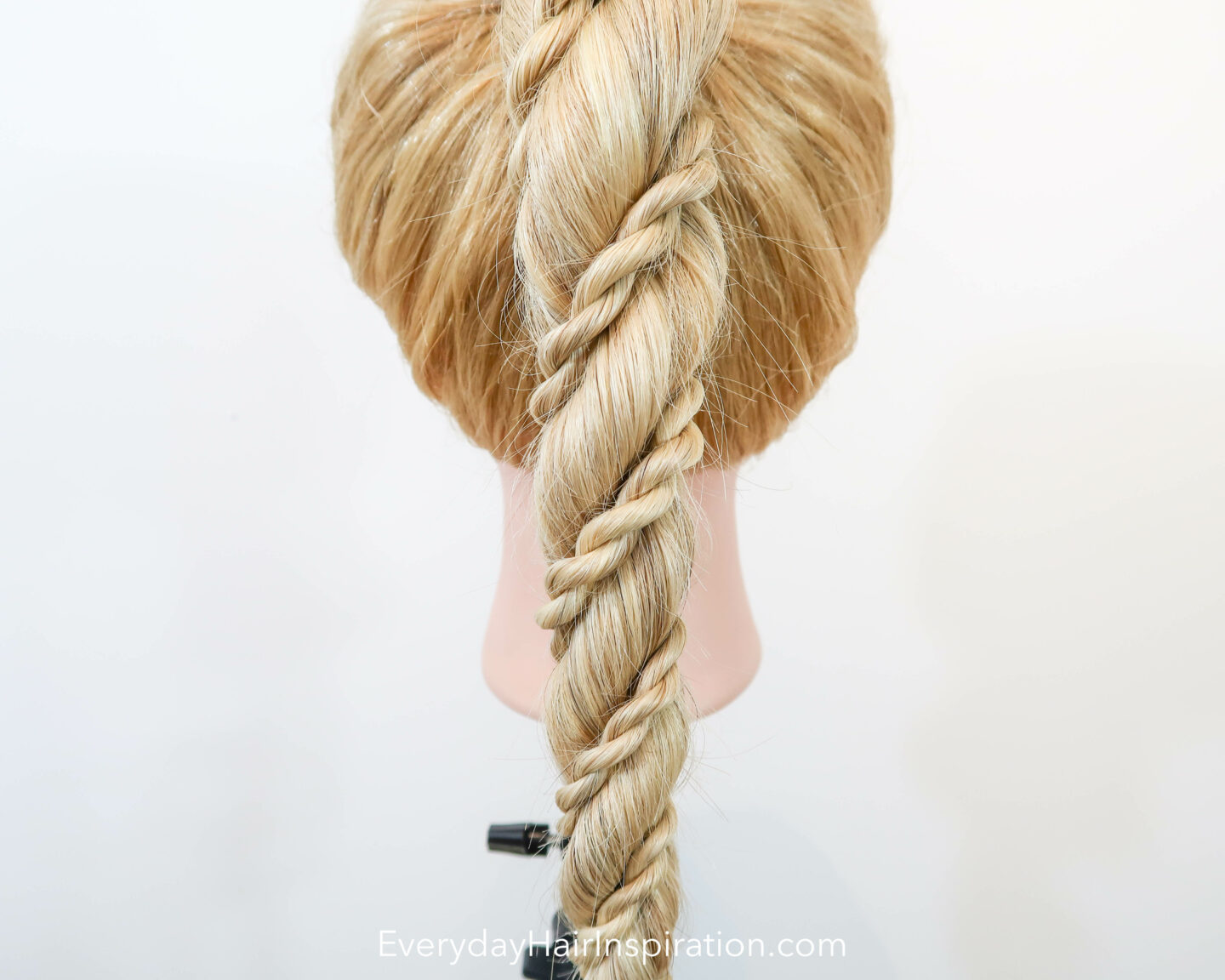 Blonde hairdresser doll seen from the back, closeup,  with a high ponytail in the hair. The ponytail is a rope braid, with 2 small rope braids wrapped around the big rope braid.