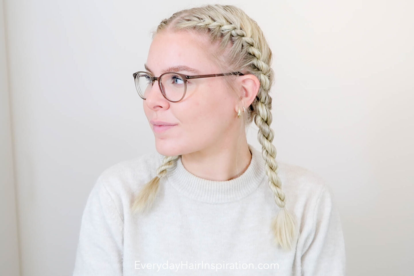 Blonde girl seen from the front, looking to the side with her hair braided into double French rope braids.